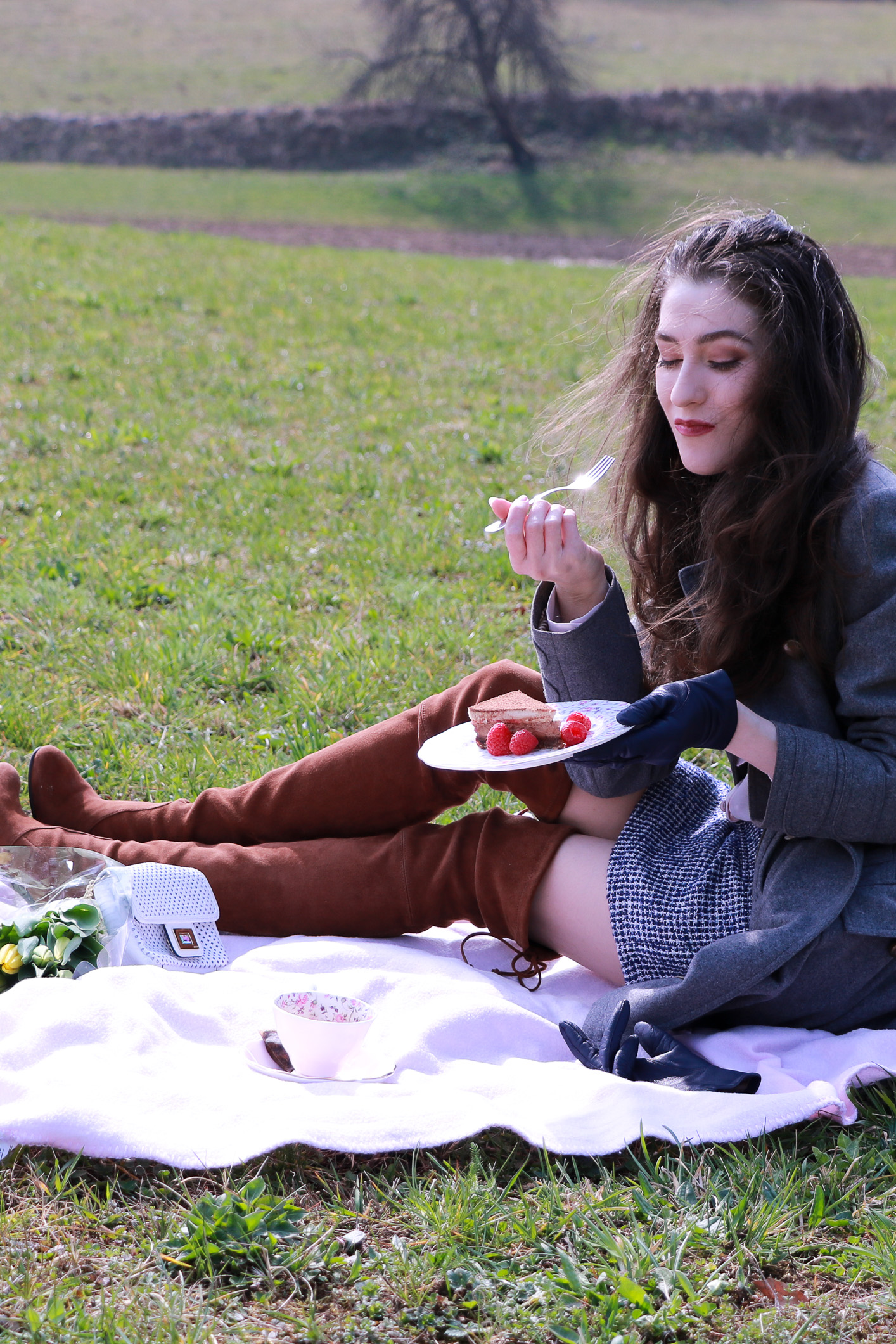 Fashion blogger Veronika Lipar of Brunette From Wall Street eating cake at the first spring picnic