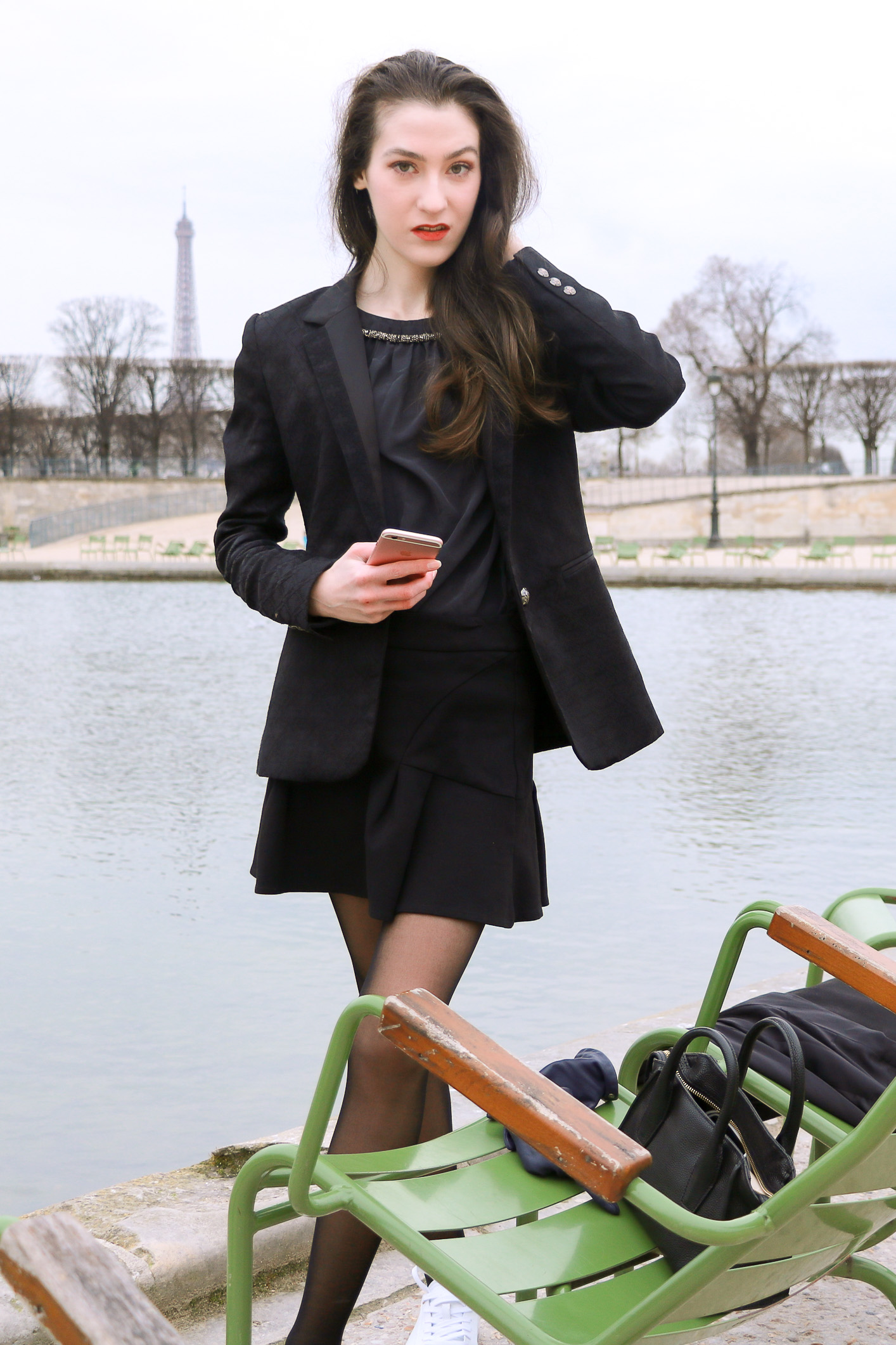 Fashion Blogger Veronika Lipar of Brunette from Wall Street sharing how to wear chic black ruffled mini skirt, sexy black tights and white sneakers like a French