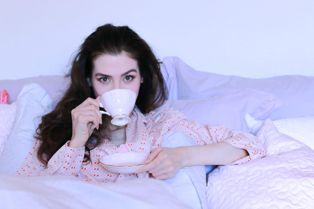 Fashion blogger Veronika Lipar of Brunette From Wall Street sipping coffee in bed