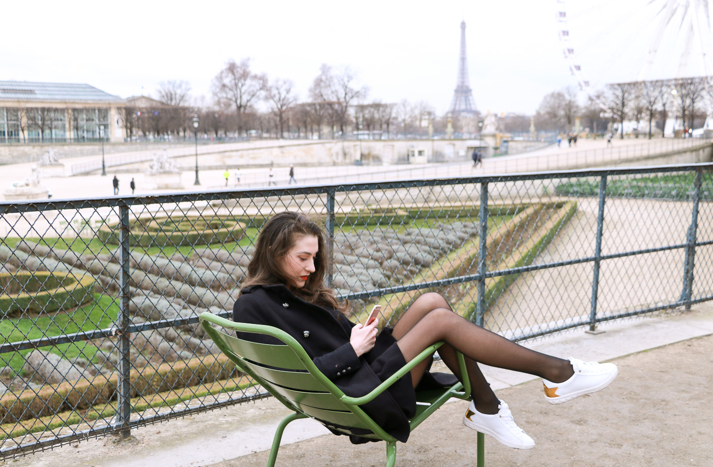 Fashion Blogger Veronika Lipar of Brunette from Wall Street sharing how to style chic black ruffled mini skirt, sexy black tights and white sneakers as a Parisian