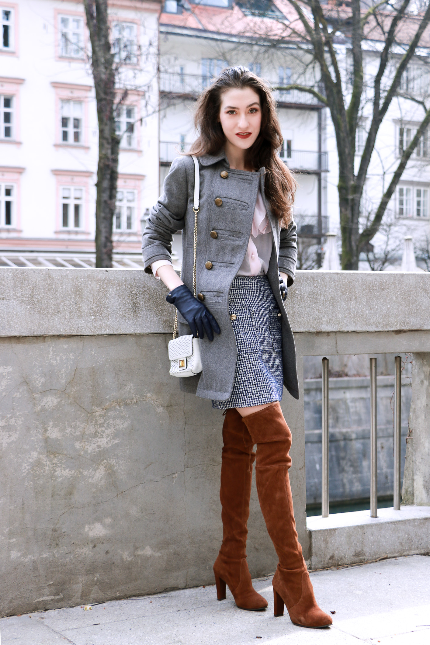 Fashion blogger Veronika Lipar of Brunette From Wall Street sharing how to style white mini bag, brown otk boots, mini blue tweed skirt, pink top and grey coat for a casual day out and about in the city