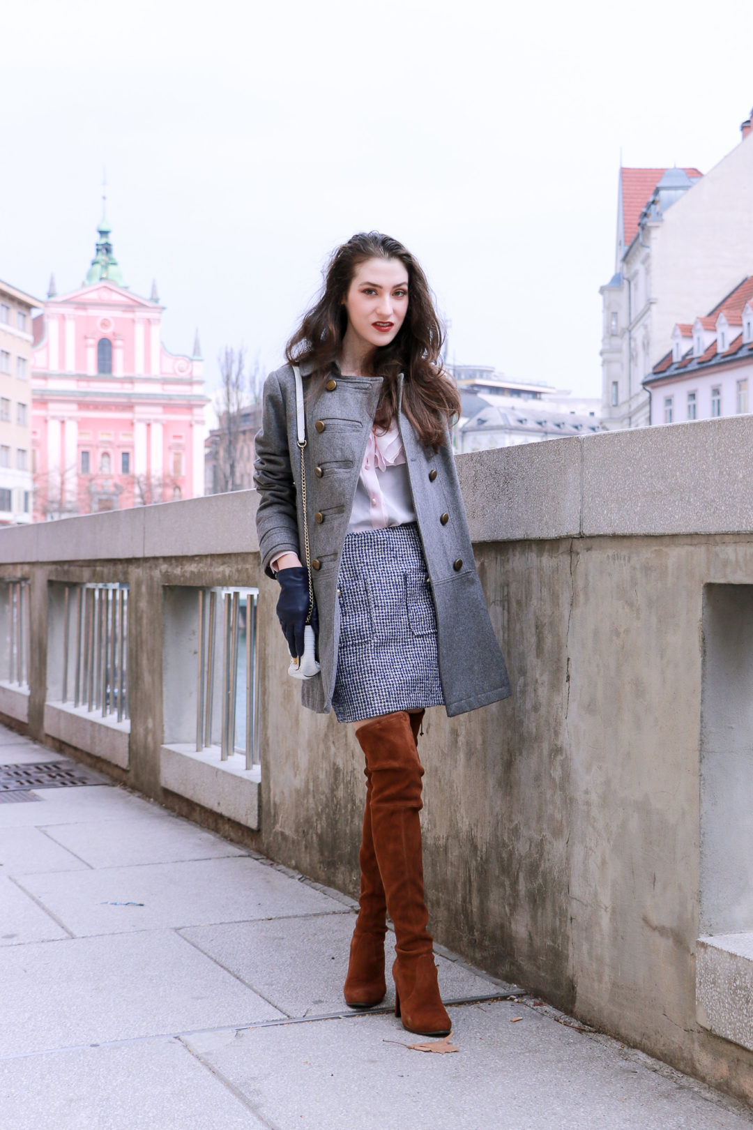 Fashion blogger Veronika Lipar of Brunette From Wall Street sharing how to wear white mini bag, brown otk boots, mini blue tweed skirt, pink top and grey coat for a coffee date with friends