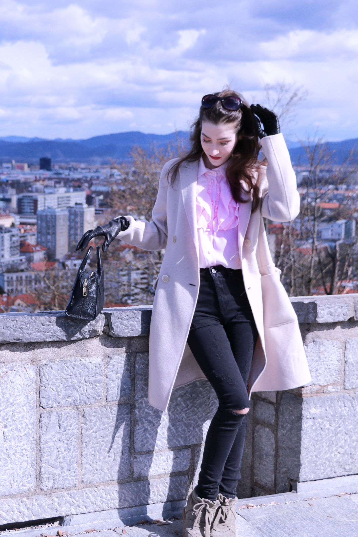Fashion blogger Veronika Lipar of Brunette From Wall Street on how to wear pink ruffled sheer blouse and black ripped jeans this spring