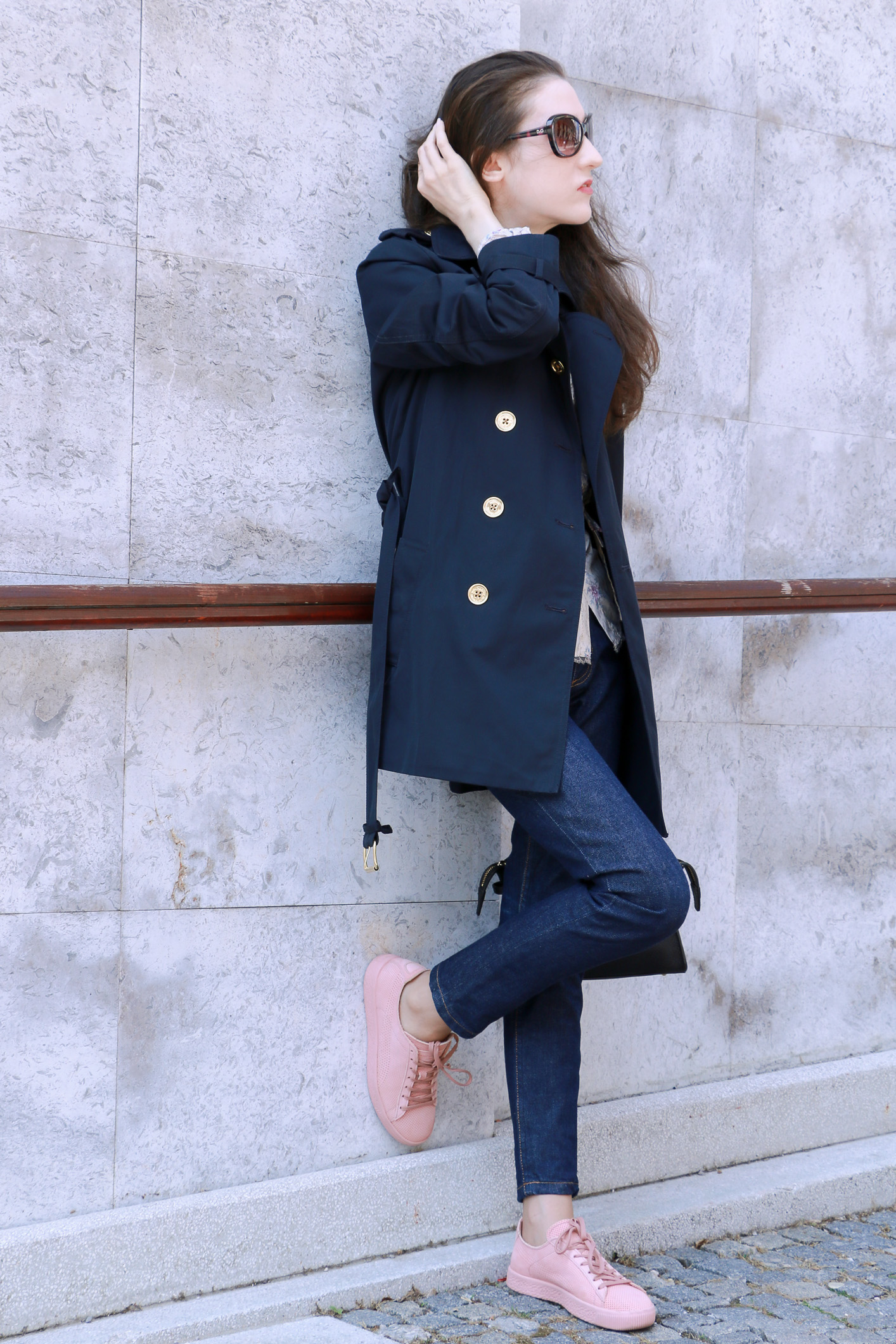 Fashion blogger Veronika Lipar of Brunette From Wall Street sharing her spring chic business style in pale pink sneakers and dark blue jeans and blue trench coat