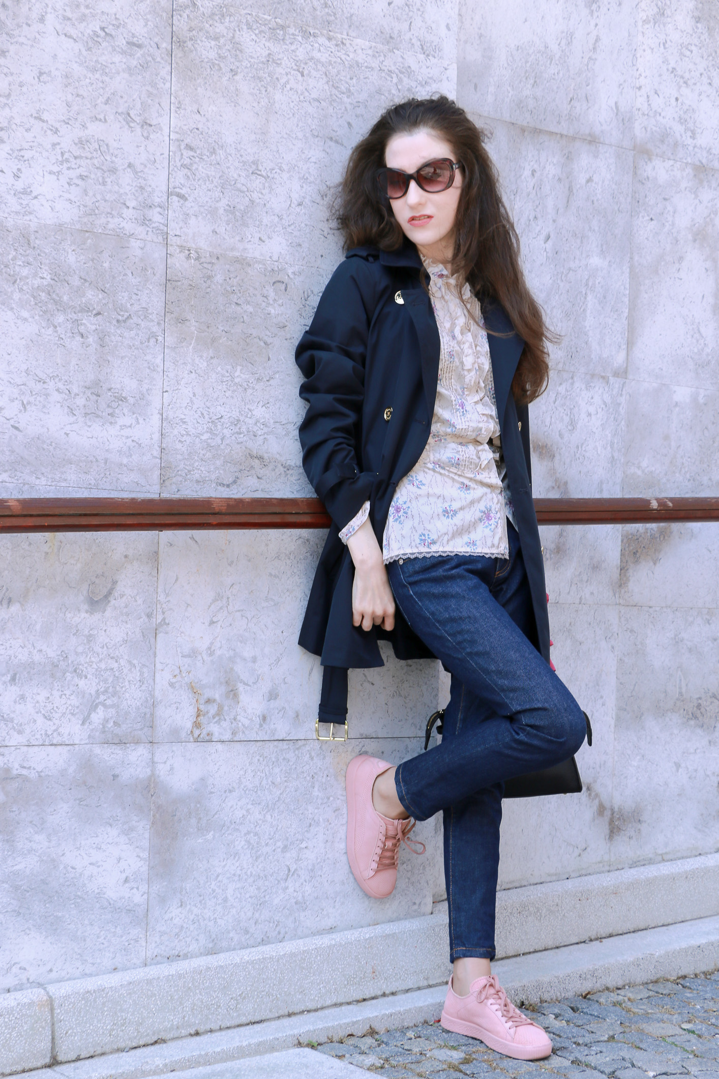 Fashion blogger Veronika Lipar of Brunette From Wall Street sharing how to wear chic business style in blue trench coat, dark blue mom jeans, pale pink sneakers, floral blouse and small black bag