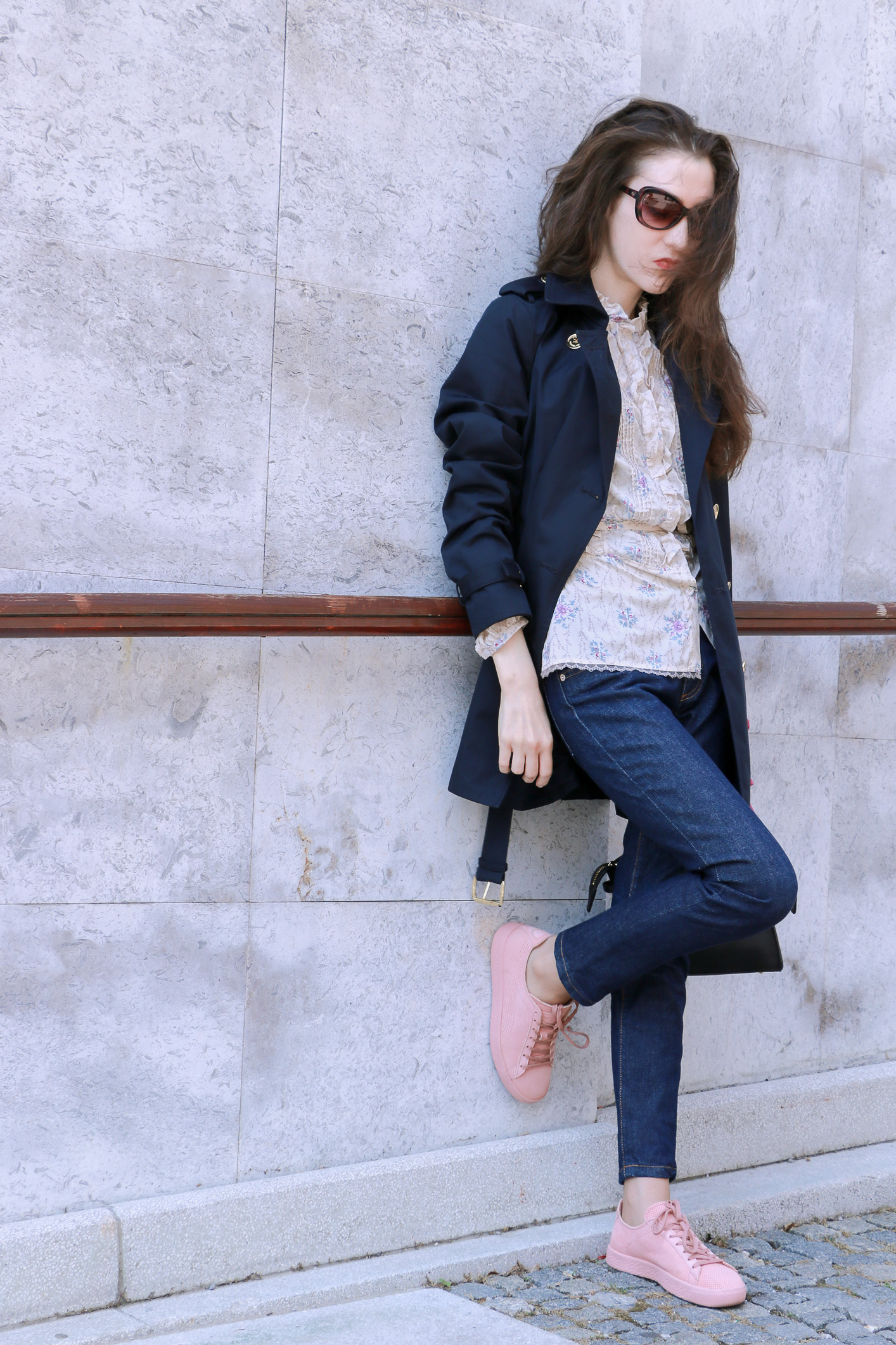 Fashion blogger Veronika Lipar of Brunette From Wall Street sharing her spring chic business outfit in pale pink sneakers and dark blue jeans and blue trench coat