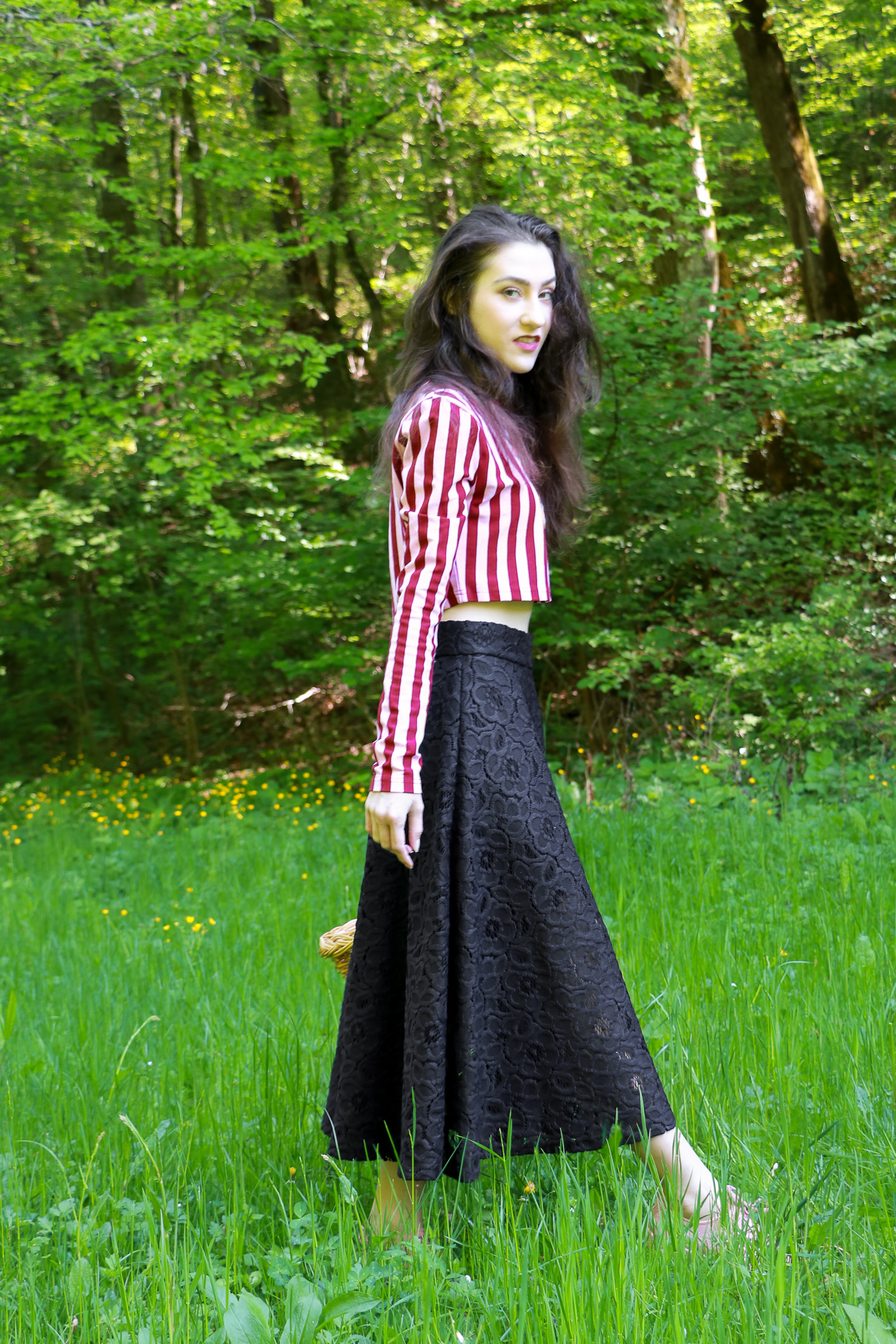 Fashion blogger Veronika Lipar of Brunette From Wall Street staring in fashion story about Easter Egg Hunt wearing pink and red stripped cropped top, black lacy midi skirt and pale pink sneakers