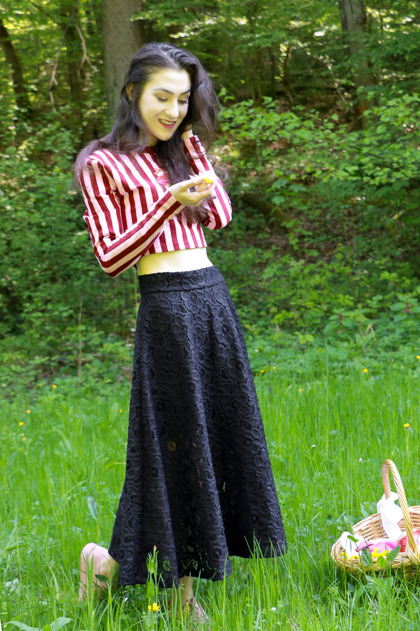 Fashion blogger Veronika Lipar of Brunette From Wall Street staring in fashion story about Chocolate Easter Egg Hunt wearing pink and red stripped cropped top, black lacy midi skirt and pale pink sneakers