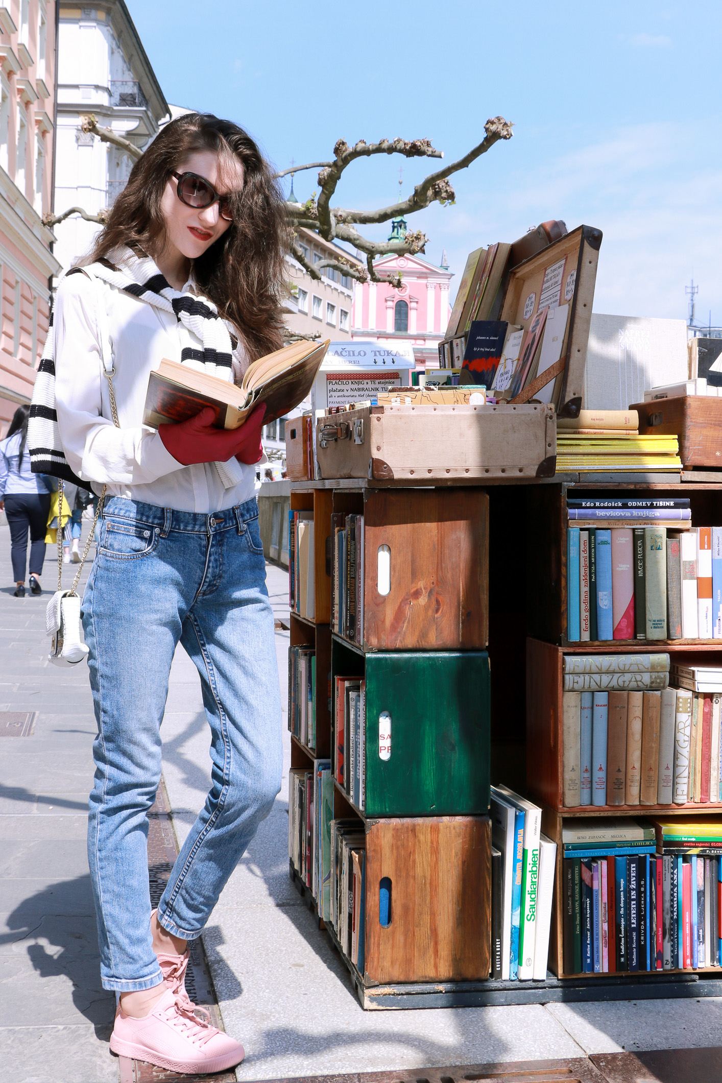 Fashion blogger Veronika Lipar of Brunette From Wall Street reading poetry, wearing light blue jeans, pale pink sneakers, black and white striped top, and white mini bag