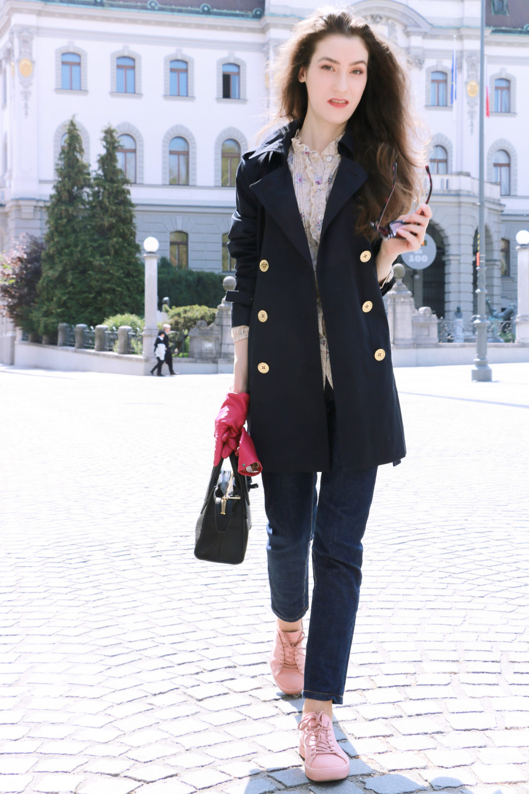Fashion blogger Veronika Lipar of Brunette From Wall Street sharing how to style blue trench coat, dark blue mom jeans, pale pink sneakers, floral blouse and small black bag for chic business style