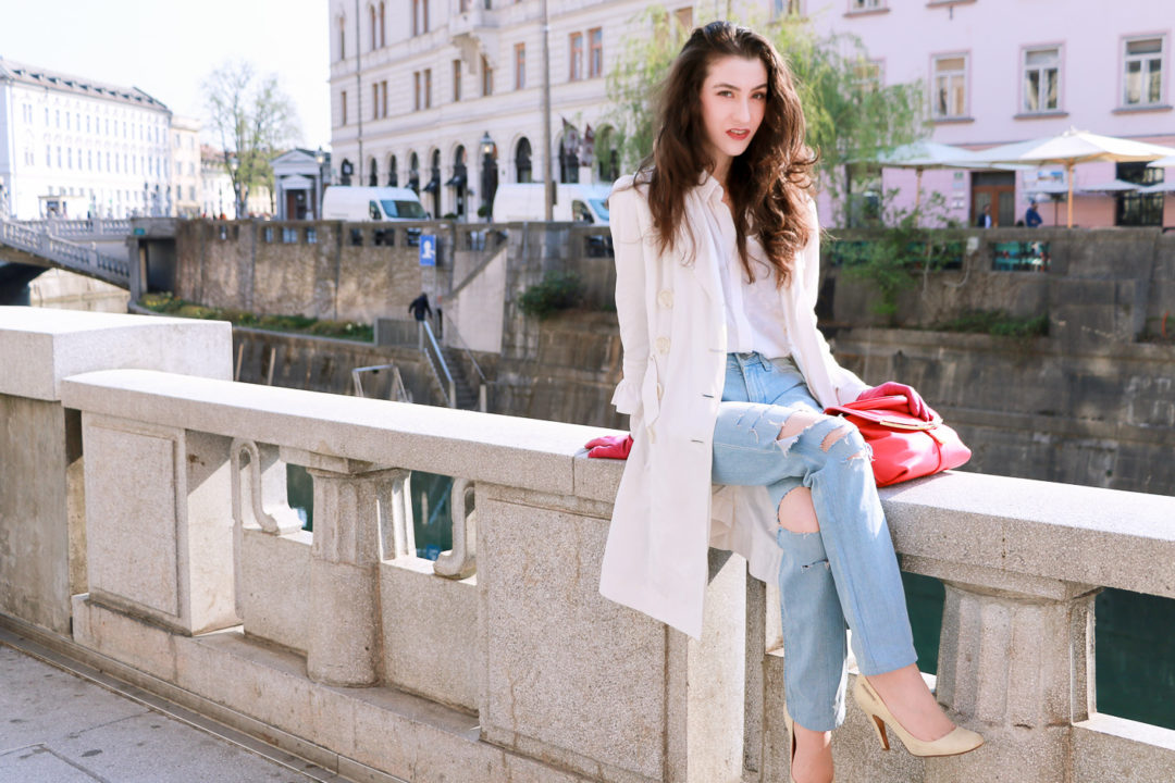 Fashion blogger Veronika Lipar of Brunette From Wall Street sharing how to style light blue ripped jeans, hot pink bag and white shoes with long thin trench coat for a casual sexy spring look