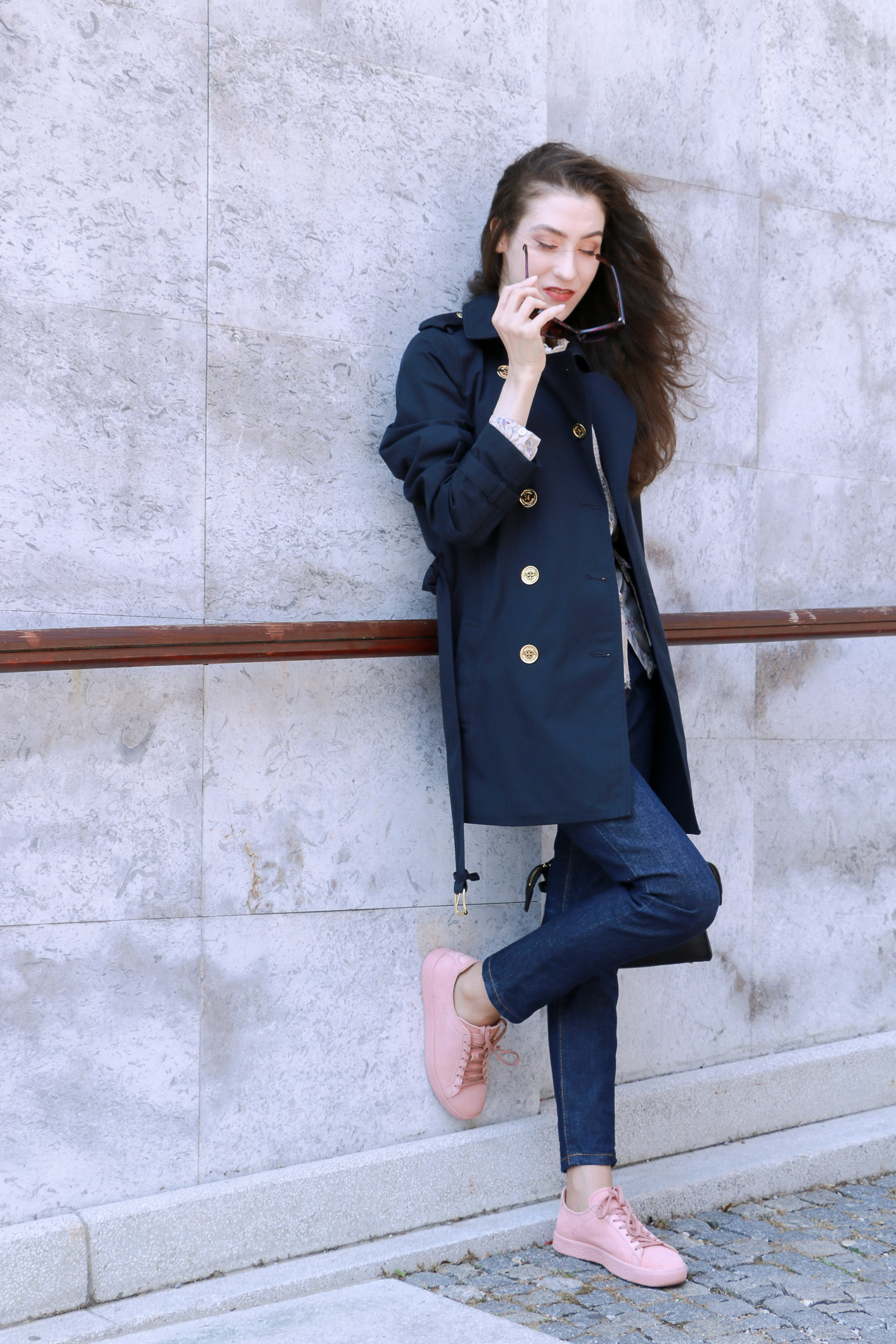 Fashion blogger Veronika Lipar of Brunette From Wall Street sharing her spring chic business look in pale pink sneakers and dark blue jeans and blue trench coat