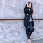 Fashion blogger Veronika Lipar of Brunette From Wall Street sharing her favourite chic business style in blue trench coat, dark blue mom jeans, pale pink sneakers, floral blouse and small black bag
