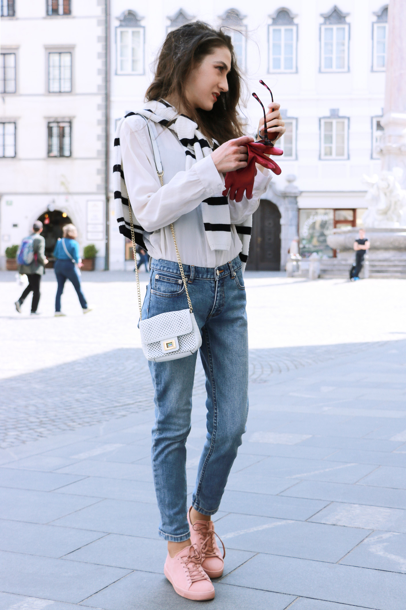 Fashion blogger Veronika Lipar of Brunette From Wall Street sharing her casual chic weekend style in light blue denim, pale pink sneakers, and black and white striped top