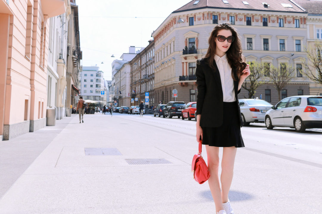 Fashion blogger Veronika Lipar of Brunette From Wall Street sharing how to style black mini skater skirt and white embellished sneakers this spring