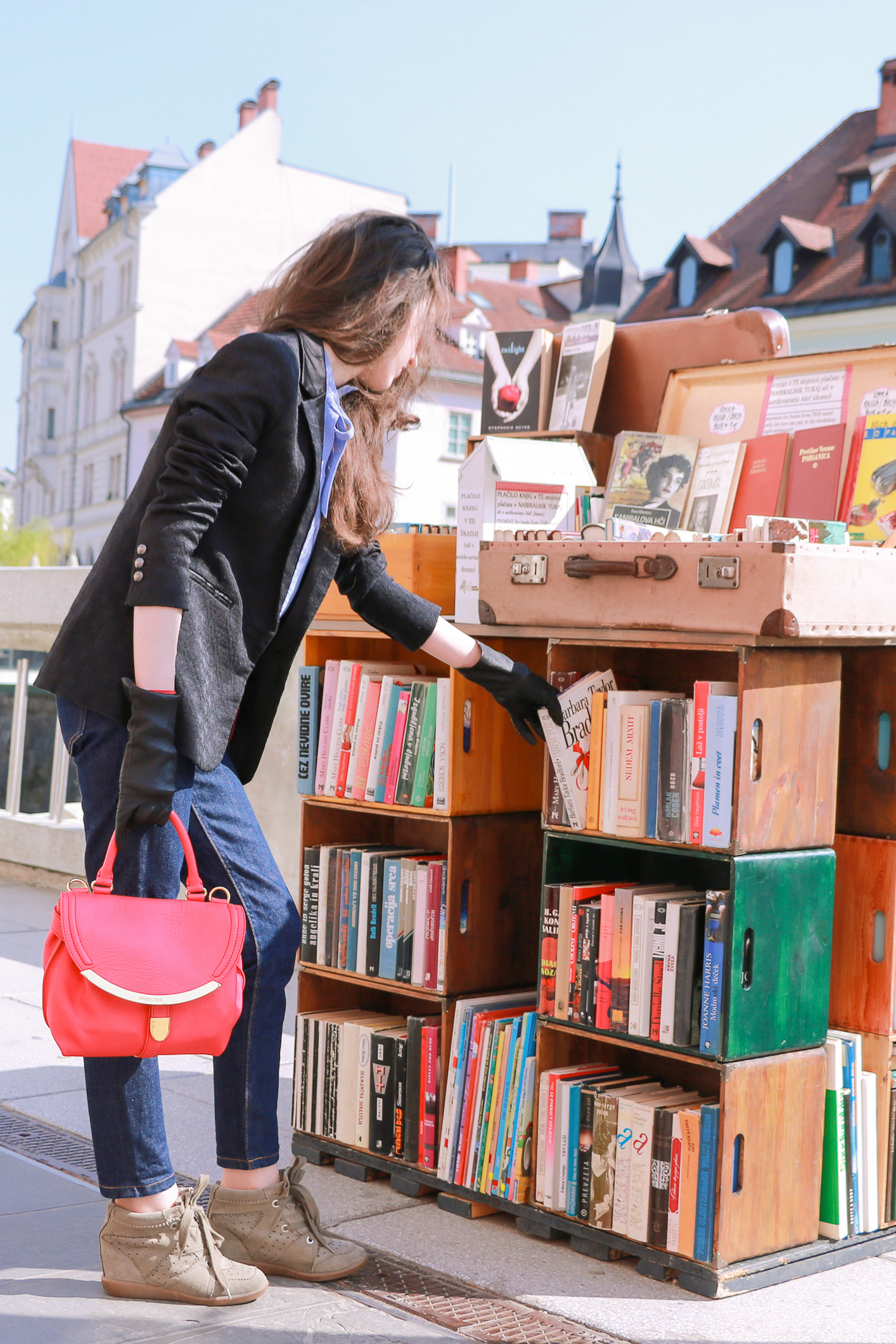 Fashion blogger Veronika Lipar of Brunette From Wall Street picking books in the library on the street