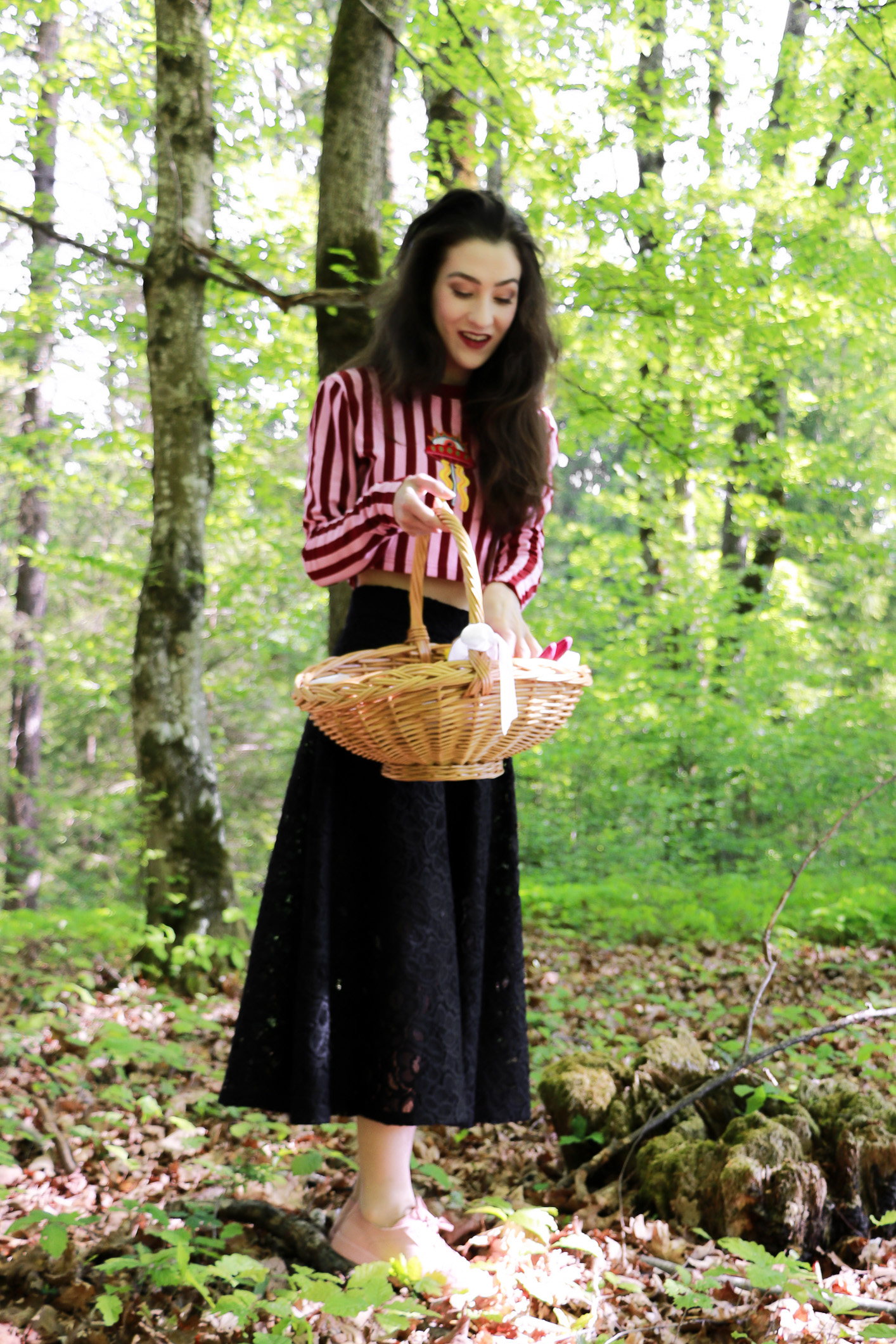 Fashion blogger Veronika Lipar of Brunette From Wall Street on how to style pink and red striped cropped top, black midi skirt and pink pale sneakers for Easter Egg hunt