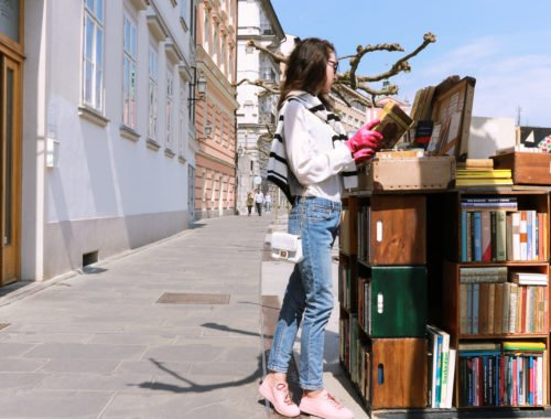 Fashion blogger Veronika Lipar of Brunette From Wall Street reading book of poems, wearing light blue jeans, pale pink sneakers, black and white striped top, and white mini bag