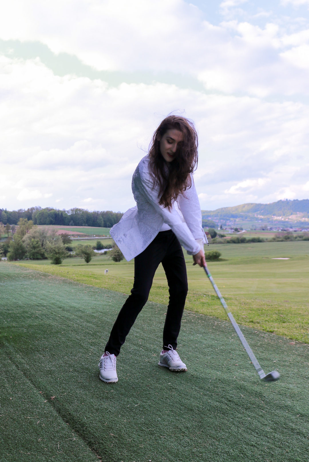 Fashion blogger Veronika Lipar of Brunette From Wall Street sharing what to wear on the golf course now to look fashionable and stylish while practicing her swing on the driving range