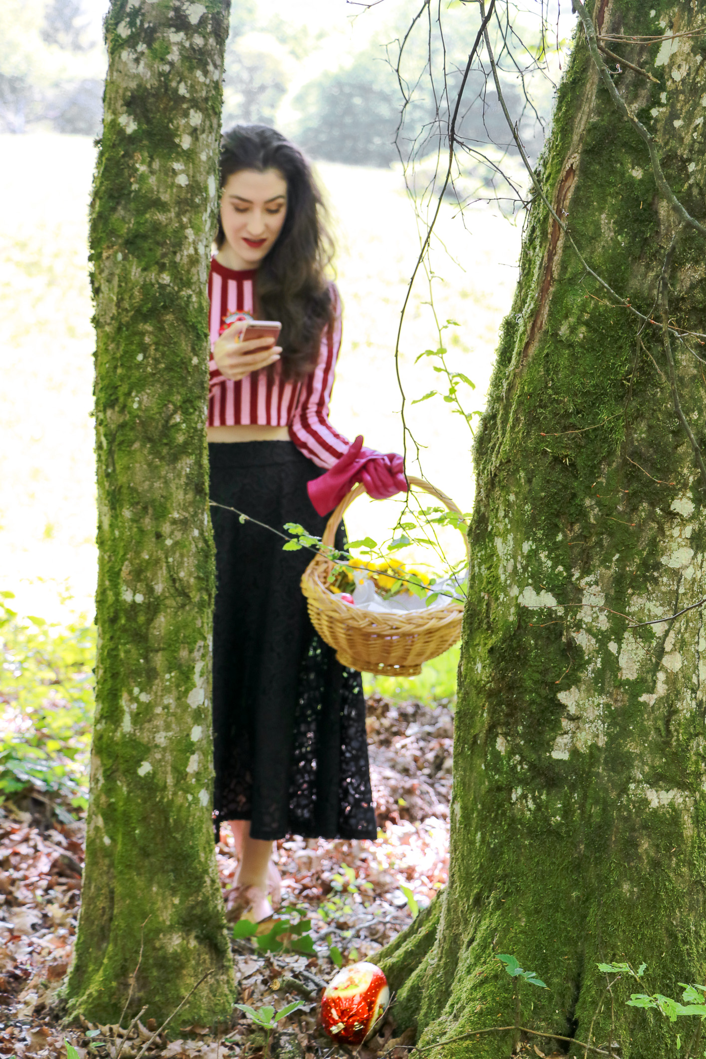 Fashion blogger Veronika Lipar of Brunette From Wall Street on how to wear pink and red striped cropped top, black midi skirt and pink pale sneakers for Easter Egg hunt
