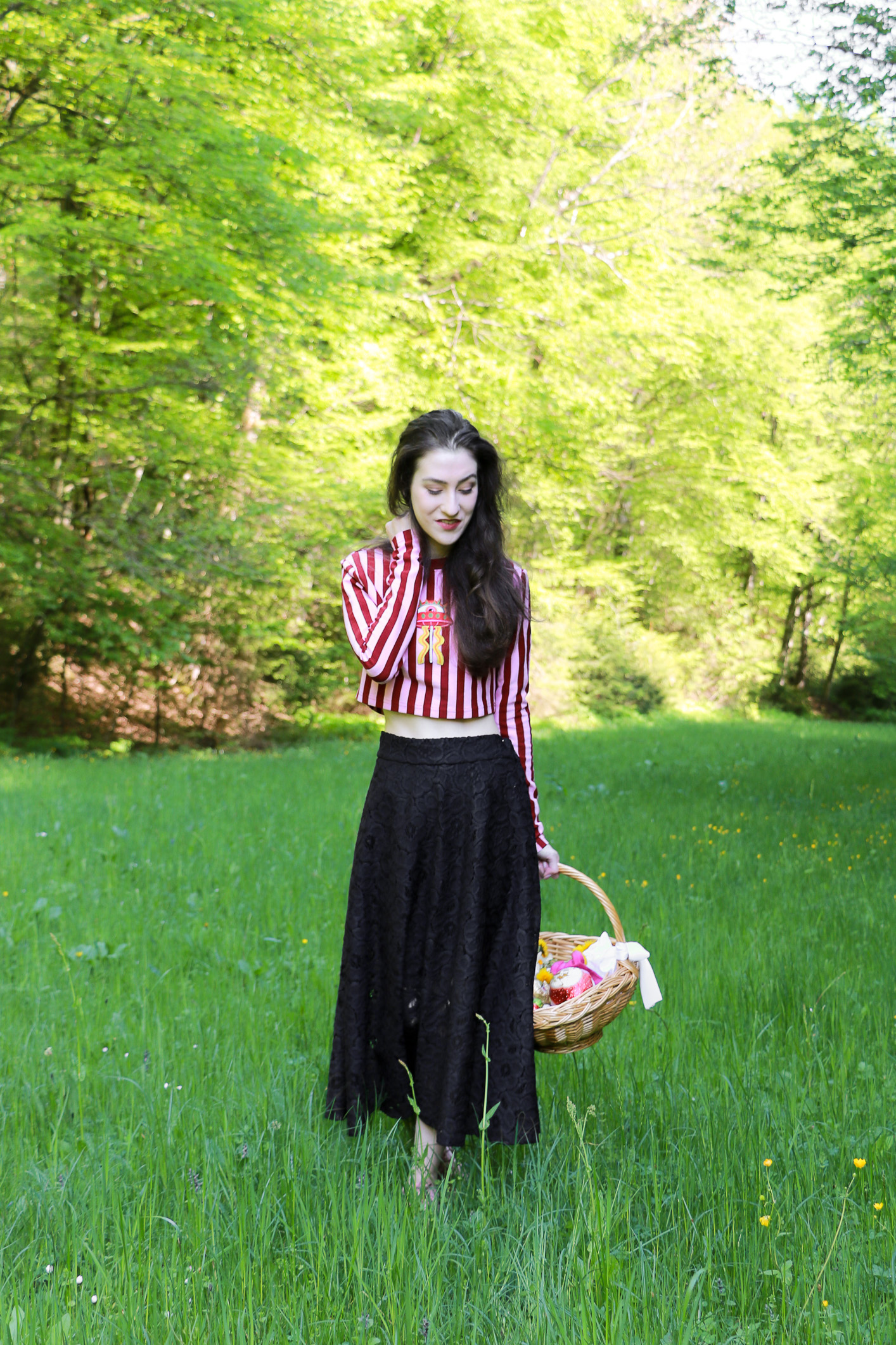 Fashion blogger Veronika Lipar of Brunette From Wall Street staring in fashion story about Easter Egg Hunt dressed in pink and red stripped cropped top, black lacy midi skirt and pale pink sneakers