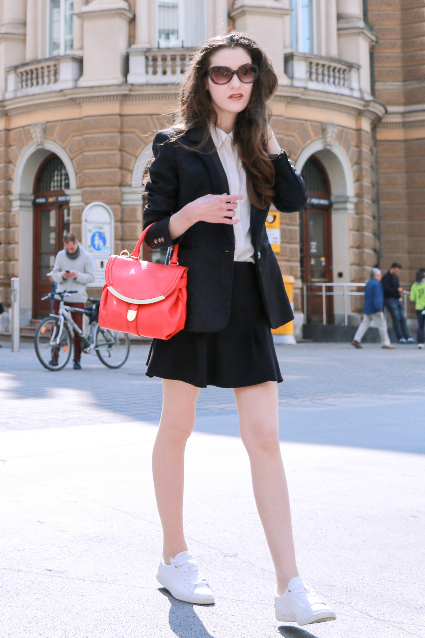 Fashion blogger Veronika Lipar of Brunette From Wall Street sharing how to style mini skirt and blazer with sneakers