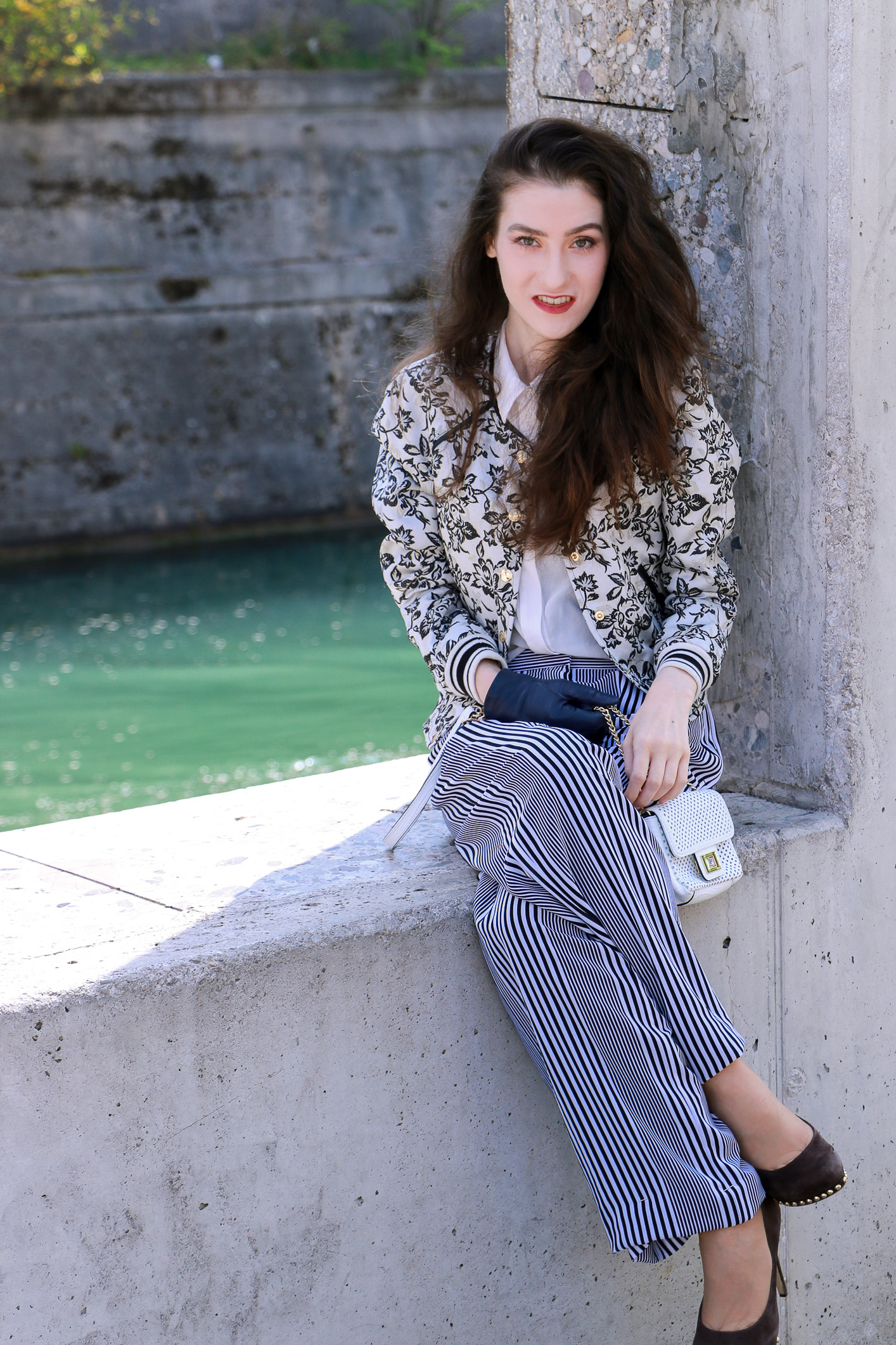 Fashion blogger Veronika Lipar of Brunette From Wall Street in Ljubljana wearing striped wide-leg pants and floral bomber jacket