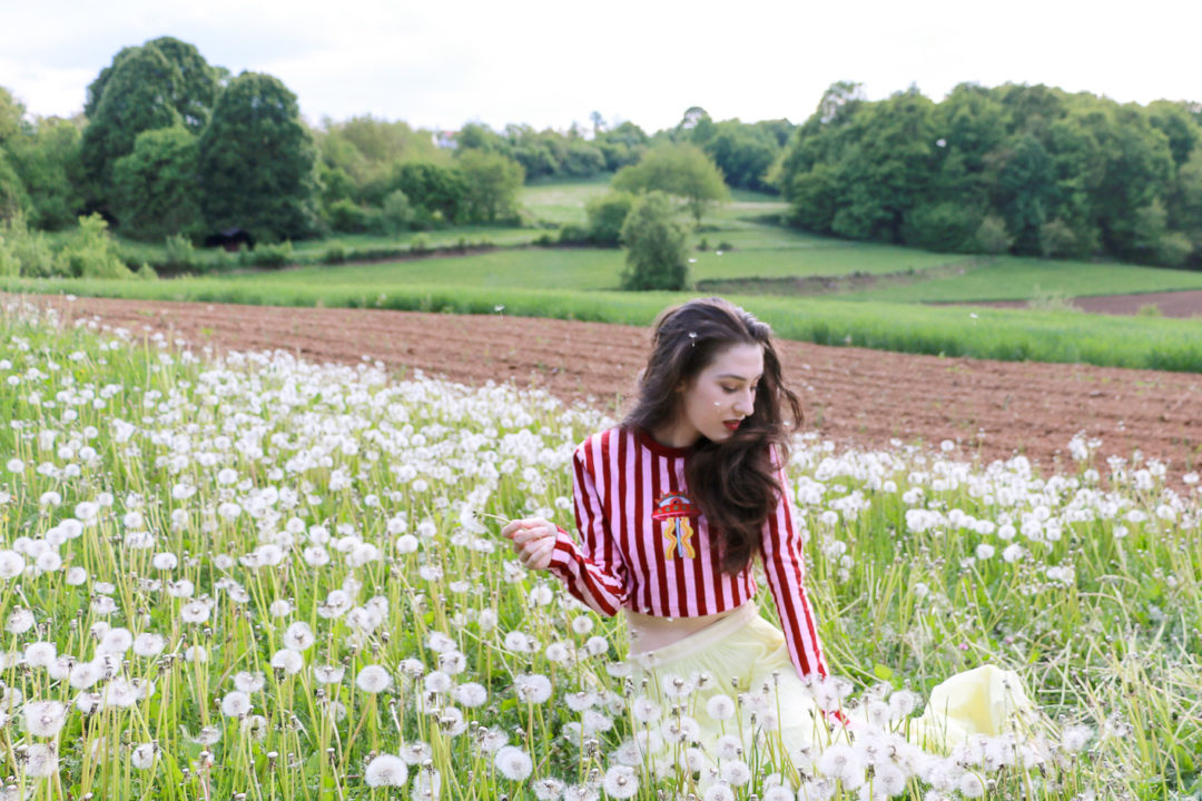 Fashion blogger Veronika Lipar of Brunette From Wall Street sitting in the field of dandelions blowing a wish dressed in long yellow tulle skirt and pink and red striped cropped top