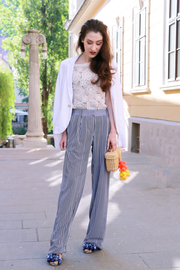 Fashion blogger Veronika Lipar of Brunette From Wall Street on how to wear striped wide-leg pants, white crochet top under the white blazer, blue Tropicana tasselled beaded sandals from Aquazzura, Nannacay's 'Baby Roge' basket bag aka mini raffia basket bag with pompoms