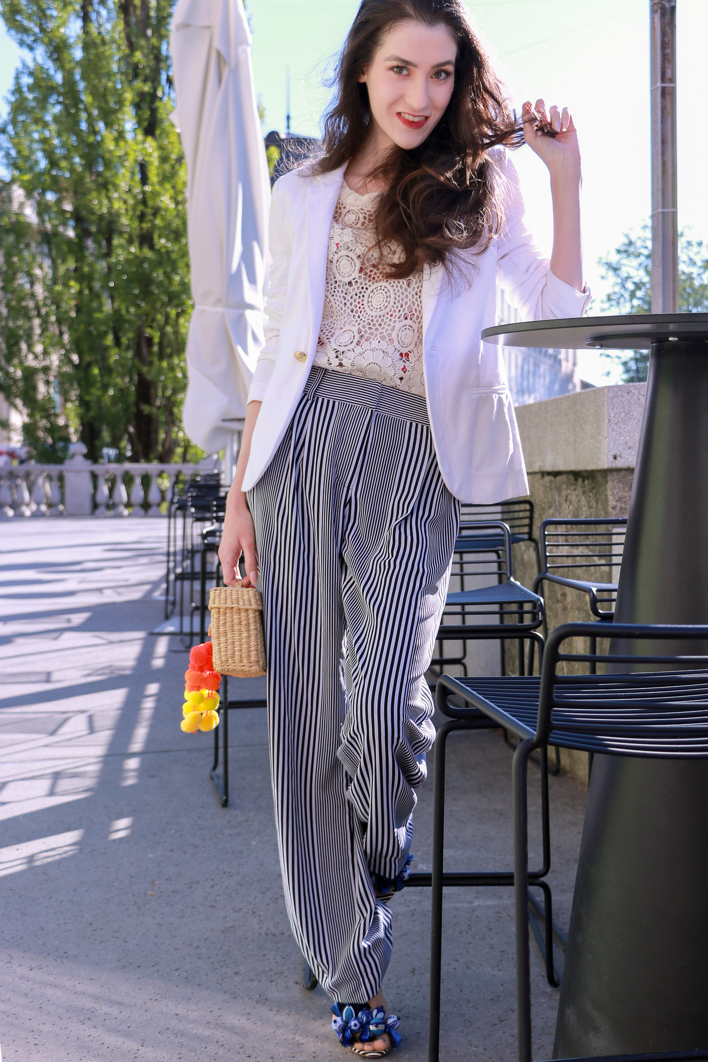 Fashion blogger Veronika Lipar of Brunette From Wall Street wearing striped wide-leg pants, white crochet top under the white blazer, blue Tropicana tasselled beaded sandals from Aquazzura, Nannacay's 'Baby Roge' basket bag aka mini raffia basket bag with pompoms