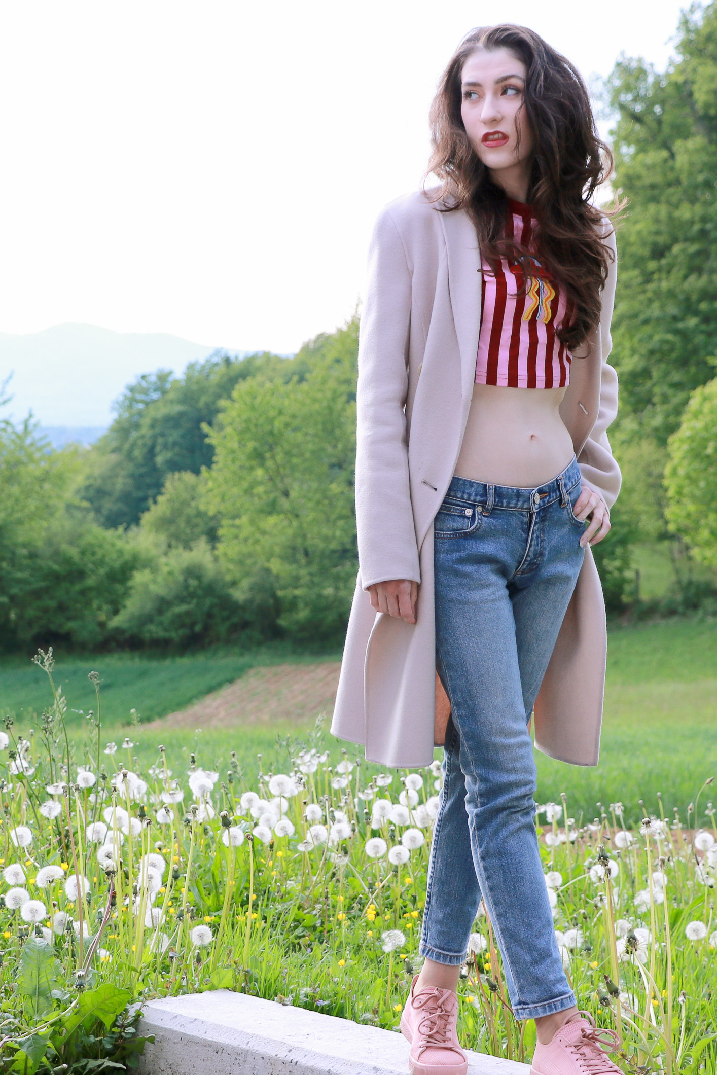 Fashion blogger Veronika Lipar of Brunette From Wall Street wearing pale pink sneakers, light blue mom jeans and striped red and pink crop top