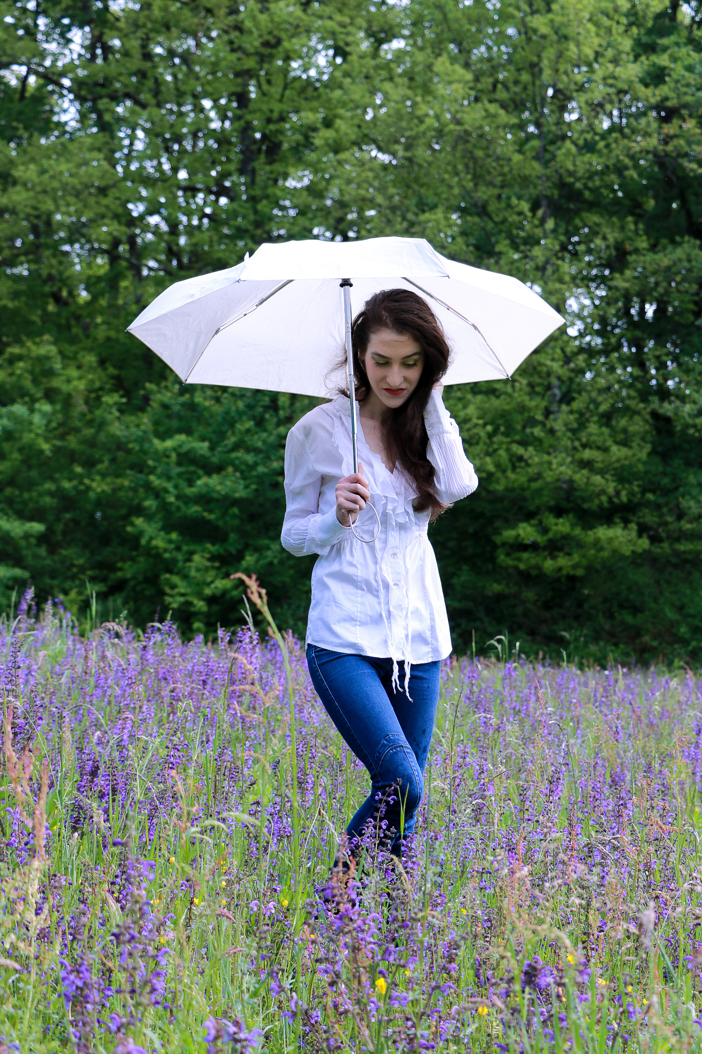 Fashion blogger Veronika Lipar of Brunette From Wall Street staring in makeup story Singing in the Rain holding an umbrella and standing in the morning rain wearing casual outfit, white fringe shirt, skinny jeans, pink Converse sneakers and bold, colourful eye makeup