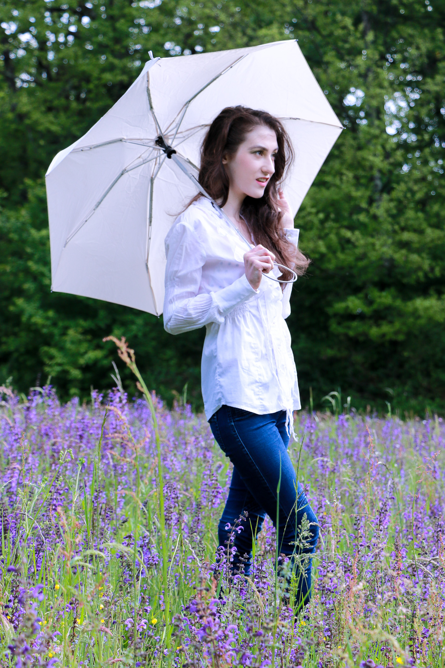 Fashion blogger Veronika Lipar of Brunette From Wall Street staring in makeup story Singing in the Rain walking through the clearing full of violet wildflowers in the middle of the forest