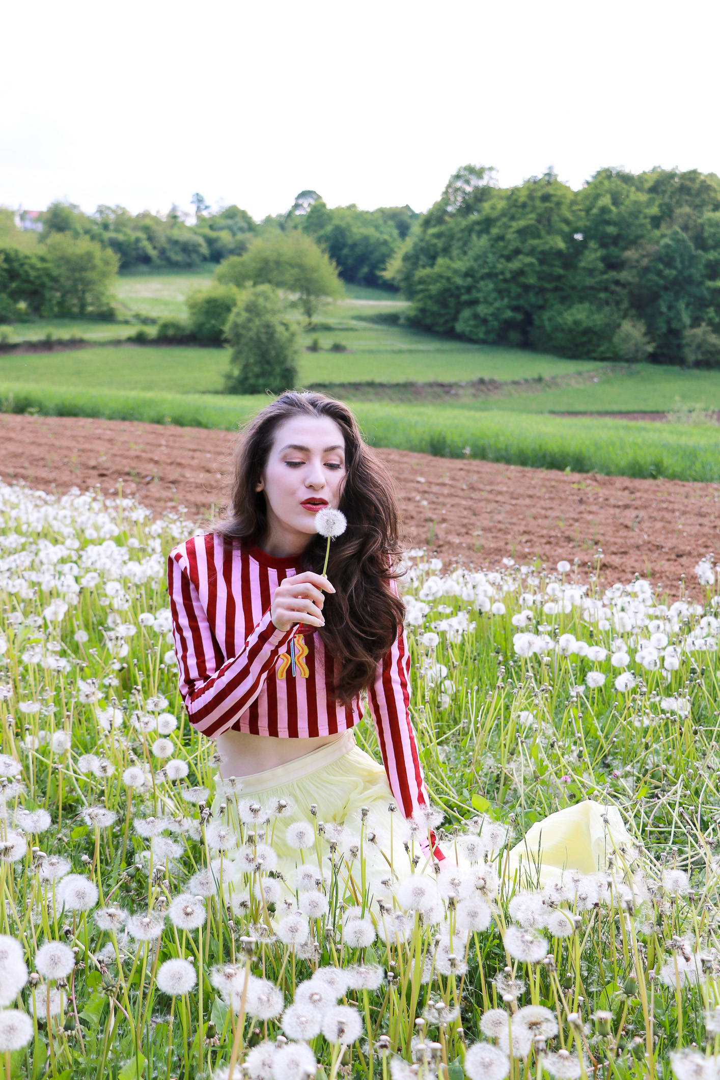 Fashion blogger Veronika Lipar of Brunette From Wall Street sitting in the field of dandelions making a wish dressed in long yellow tulle skirt and pink and red striped cropped top