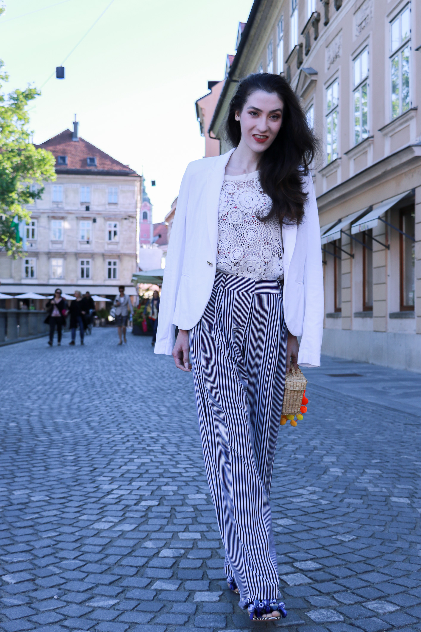 Fashion blogger Veronika Lipar of Brunette From Wall Street on her morning stroll through the city wearing striped wide-leg pants, crochet top, pom pom sandals and raffia basket bag
