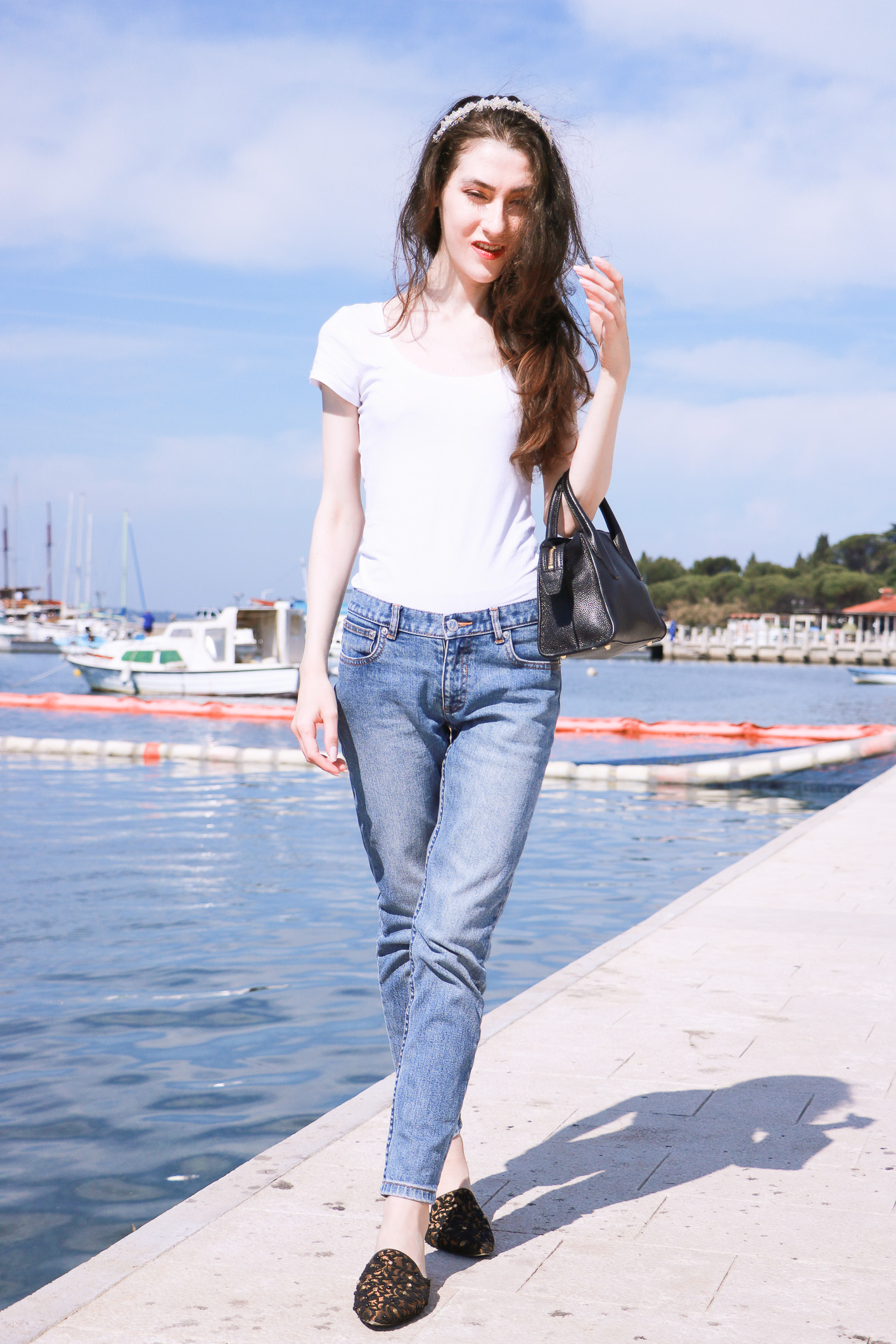 Fashion blogger Veronika Lipar of Brunette From Wall Street sharing 5 accessories that makes us look elegant in white tee shirt and light blue mom jeans while by the Adriatic sea