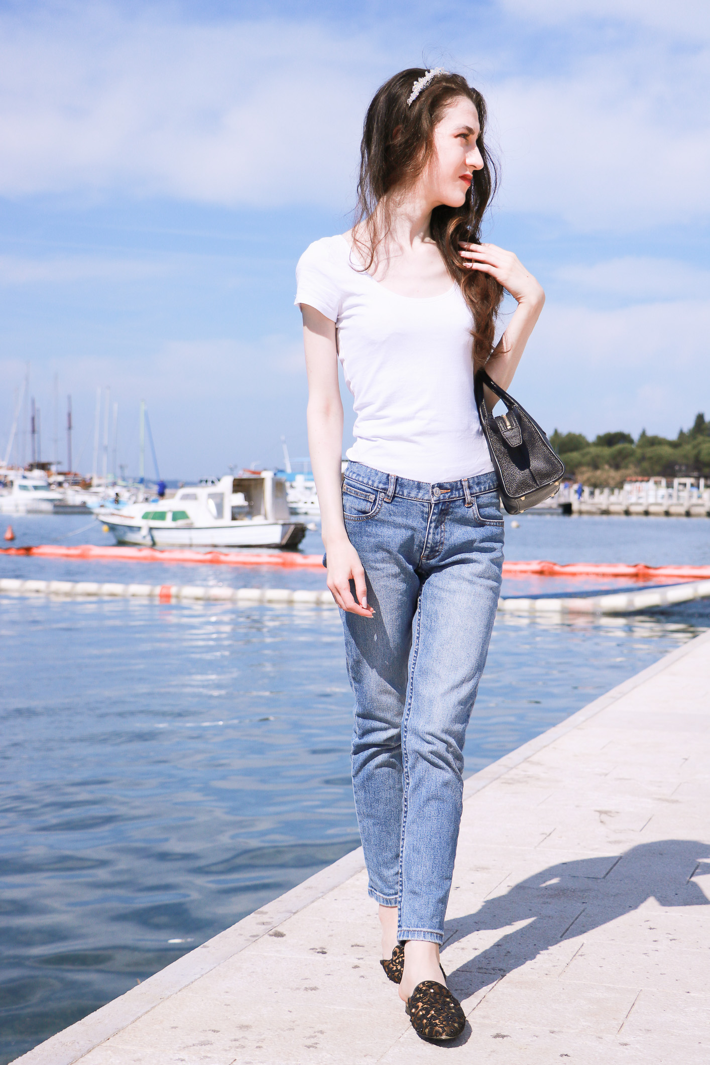 Fashion blogger Veronika Lipar of Brunette From Wall Street sharing how to elevate a white tee shirt and light blue mom jeans while by the Adriatic sea