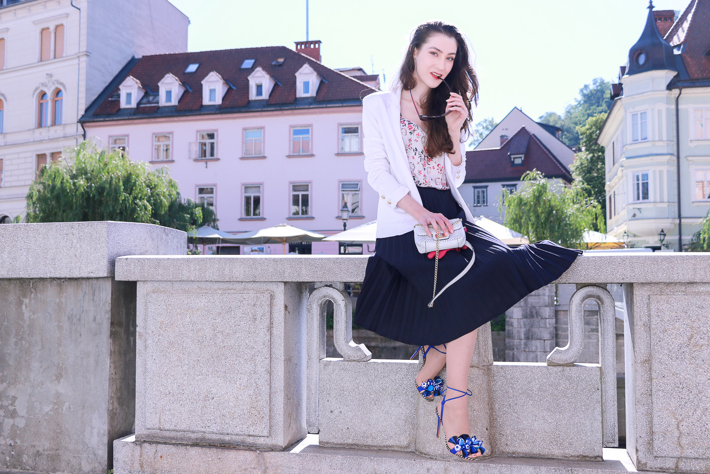 Fashion blogger Veronika Lipar of Brunette From Wall Street in Ljubljana wearing black vintage midi pleated skirt, blue Tropicana tasseled beaded sandals from Aquazzura, floral top, and white blazer