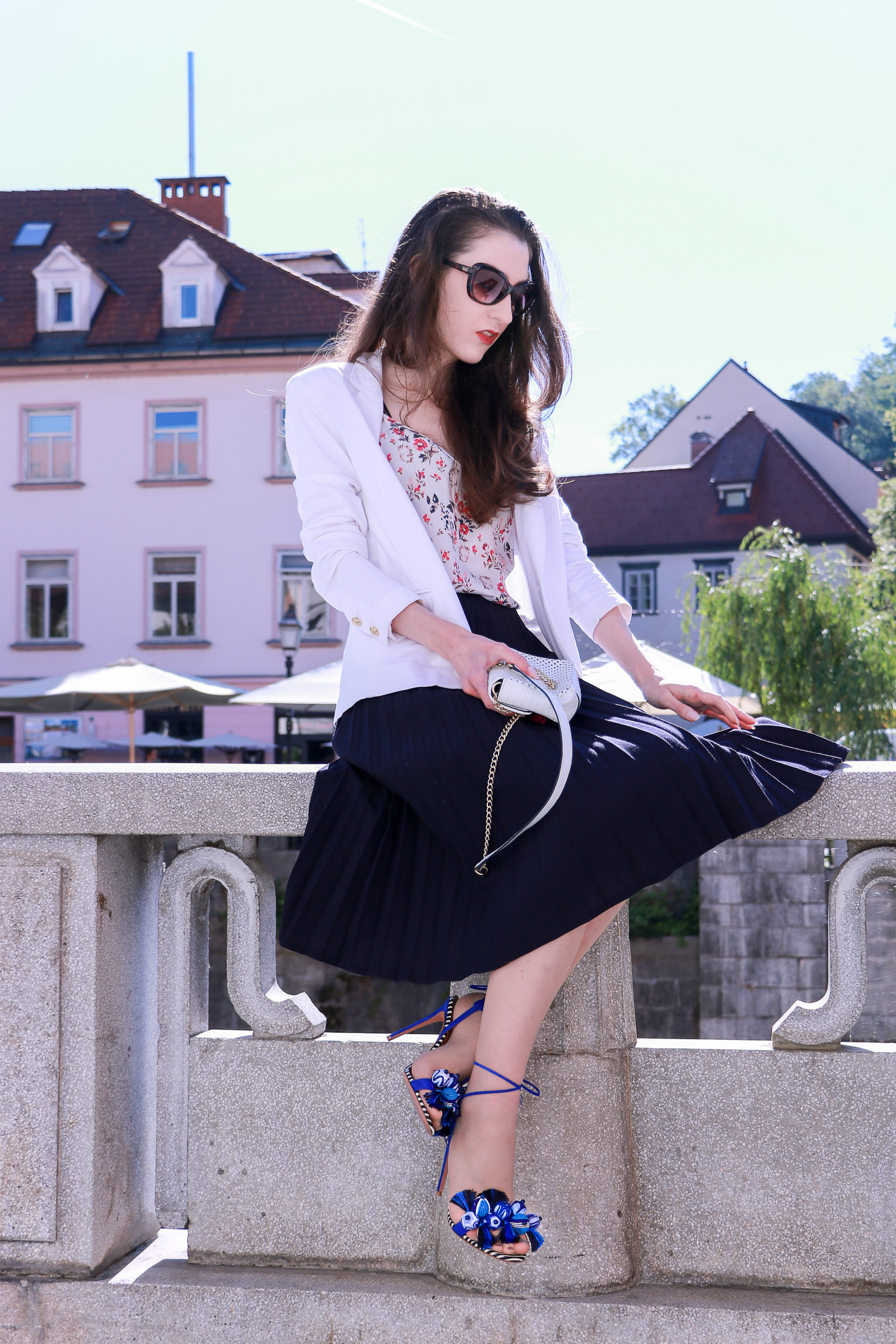 Fashion blogger Veronika Lipar of Brunette From Wall Street sharing how to style black vintage pleated midi skirt, blue Tropicana tasseled beaded sandals from Aquazzura, floral top, and white blazer for a chic summer look