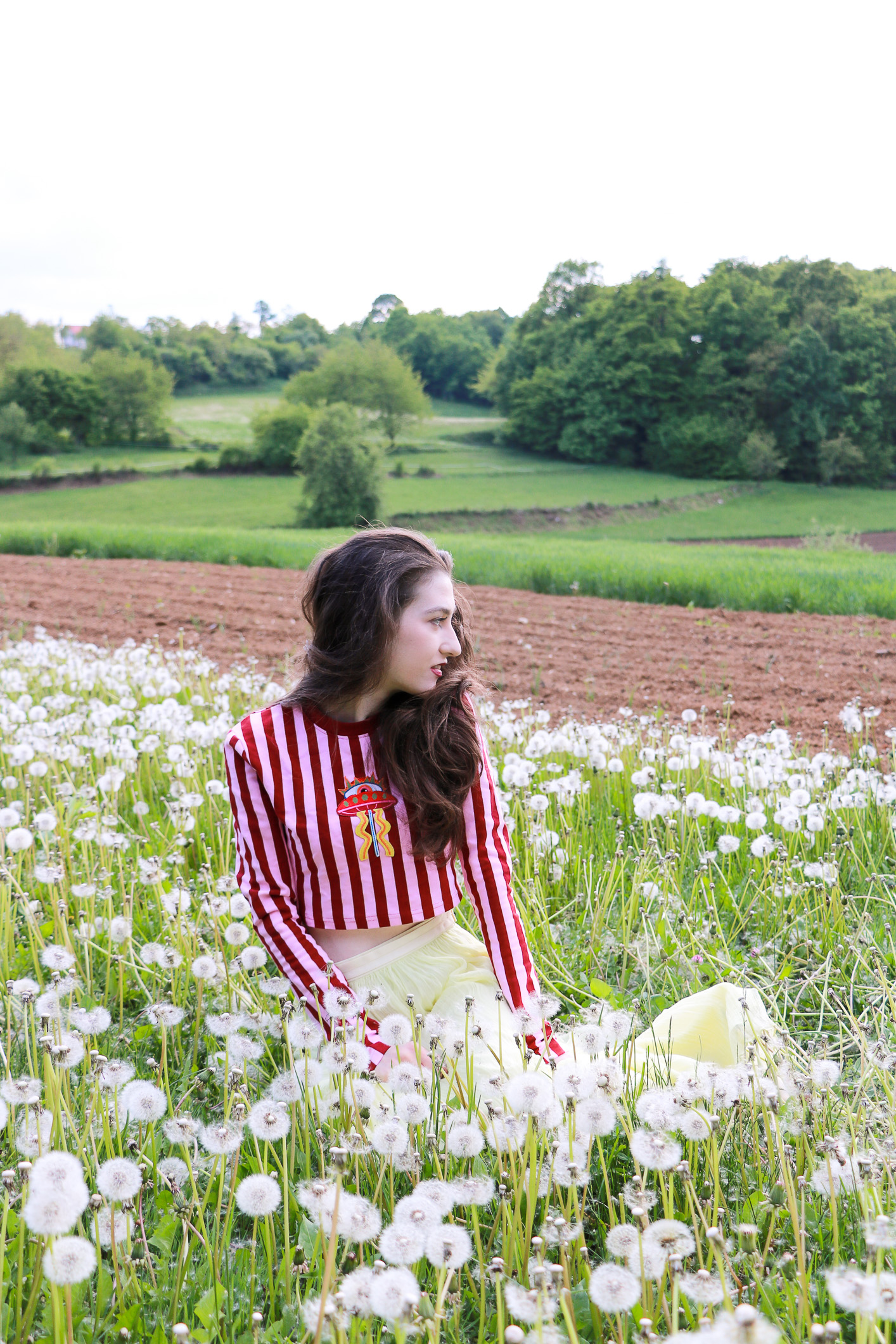 Fashion blogger Veronika Lipar of Brunette From Wall Street sitting in the field of dandelions making a wish dressed in long yellow tulle skirt and pink and red striped crop top
