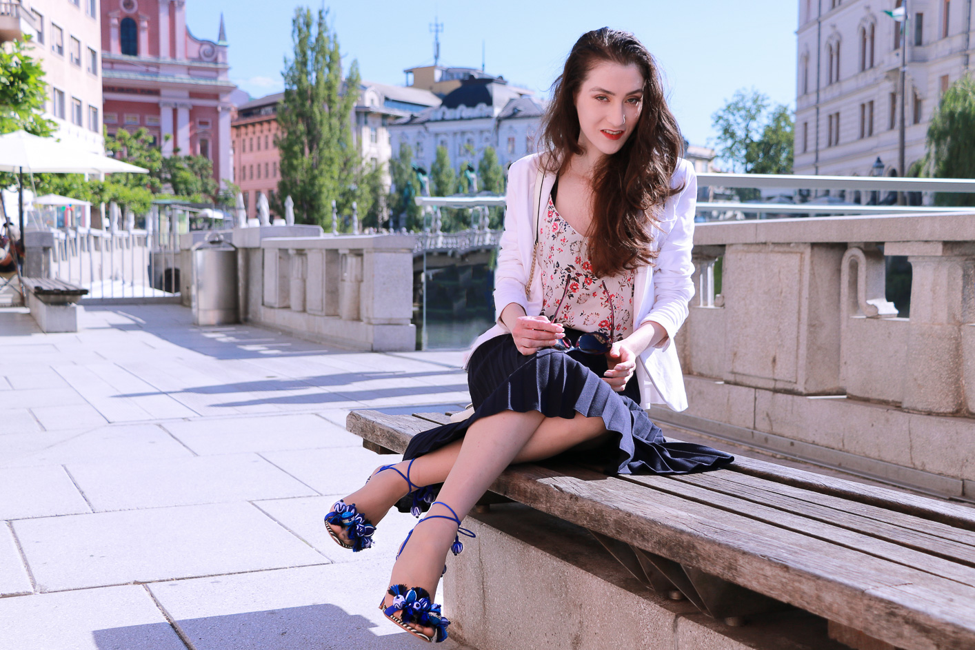 Fashion blogger Veronika Lipar of Brunette From Wall Street sharing how to style black vintage midi plissé skirt, blue Tropicana tasseled beaded sandals from Aquazzura, floral top, and white blazer for a chic summer look