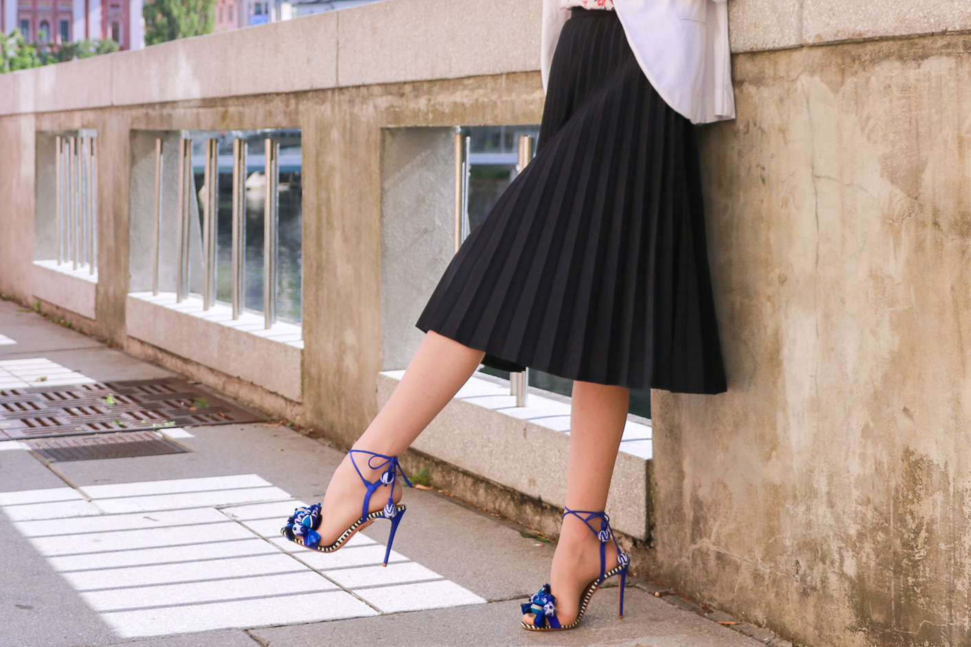Fashion blogger Veronika Lipar of Brunette From Wall Street in Ljubljana dressed in black vintage pleated midi skirt, blue Tropicana tasseled beaded sandals from Aquazzura, floral top, and white blazer for a chic street style look