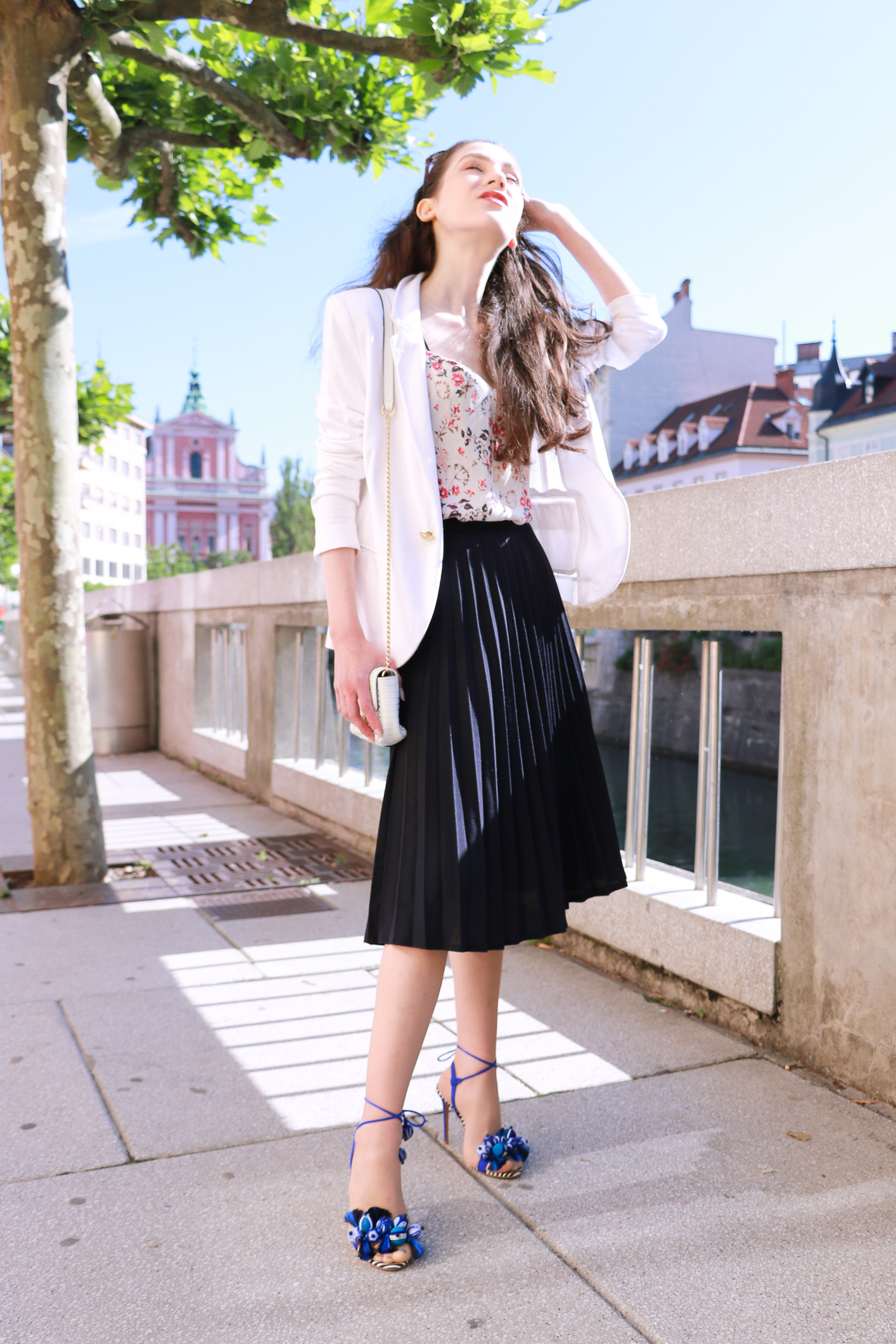 Fashion blogger Veronika Lipar of Brunette From Wall Street sharing how to wear black vintage pleated midi skirt, blue Tropicana tasseled beaded sandals from Aquazzura, floral top, and white blazer for a chic street style look