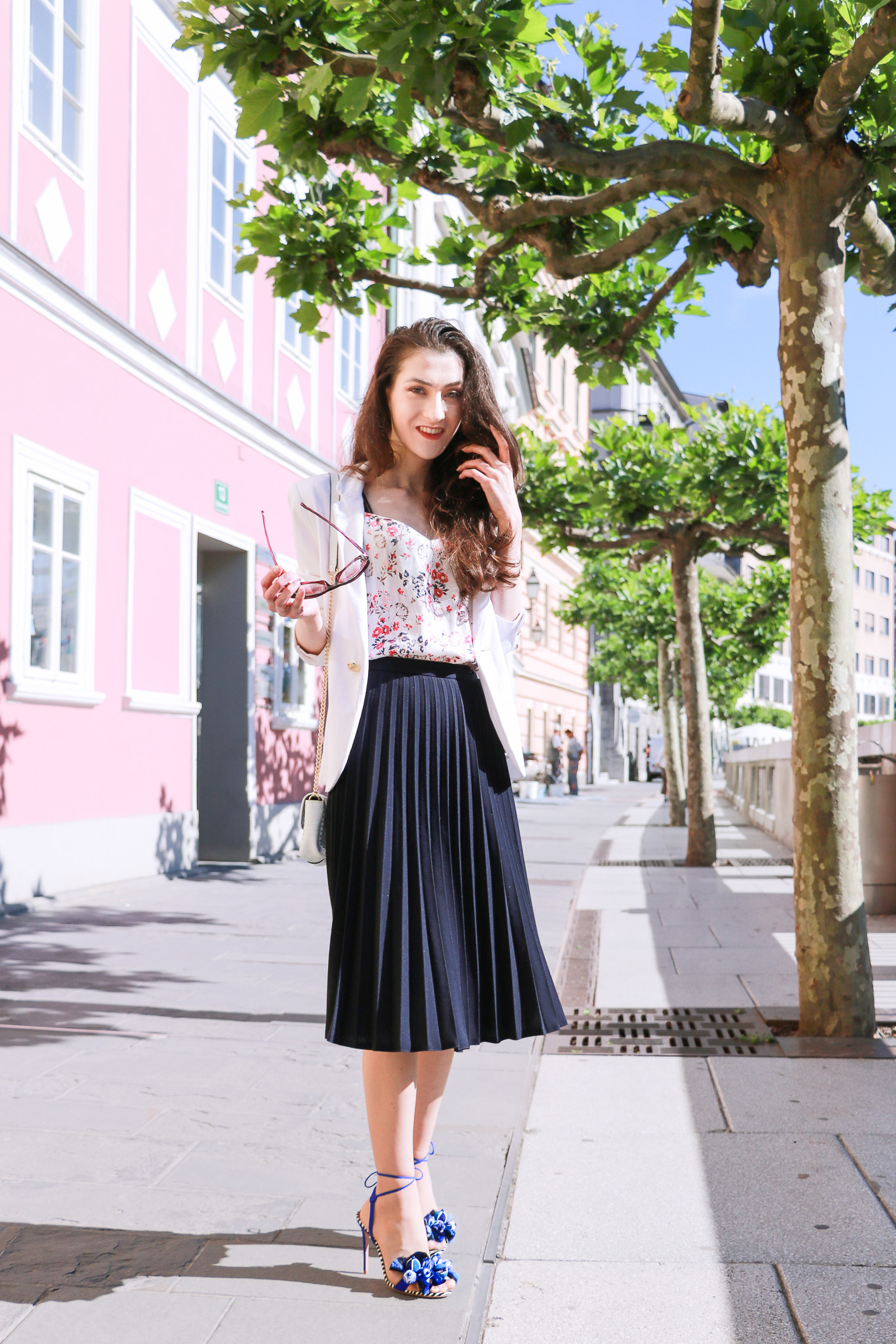 Fashion blogger Veronika Lipar of Brunette From Wall Street sharing how to wear black vintage midi pleated skirt, blue Tropicana tasseled beaded sandals from Aquazzura, floral top, and white blazer for a chic summer look