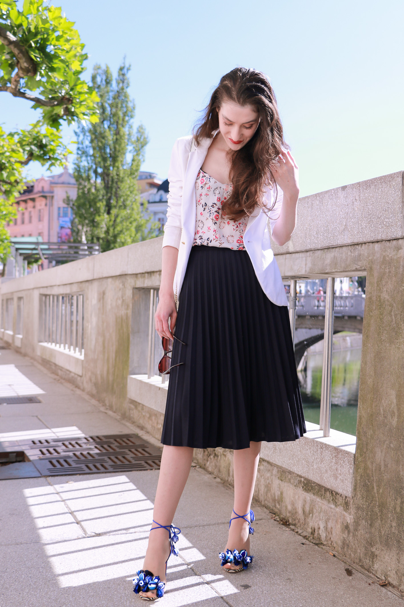 Fashion blogger Veronika Lipar of Brunette From Wall Street sharing how to style black vintage midi pleated skirt, blue Tropicana tasseled beaded sandals from Aquazzura, floral top, and white blazer for a chic summer look