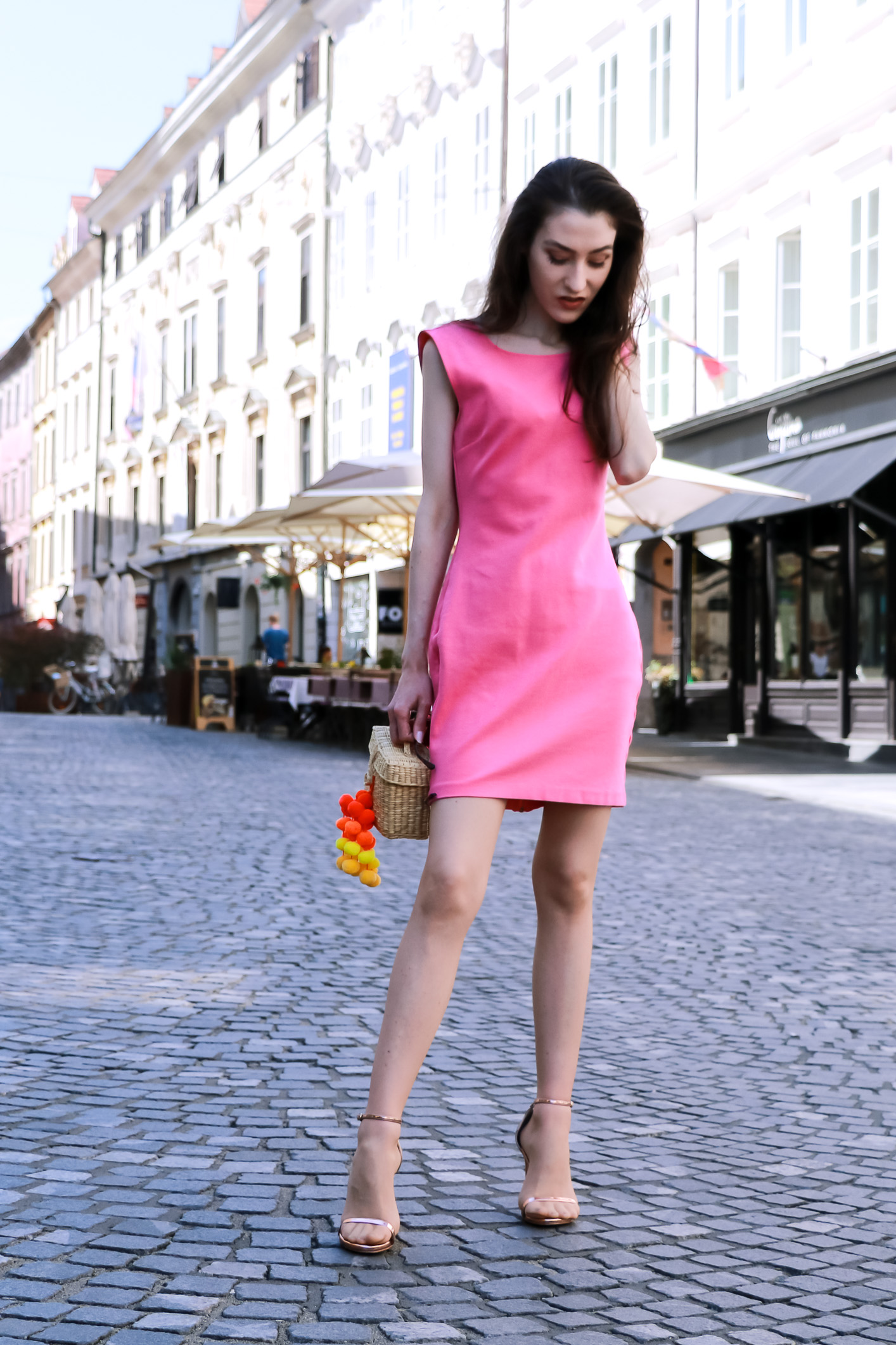 Fashion blogger Veronika Lipar of Brunette From Wall Street sharing how to wear pink cocktail dress, rose gold sandals and raffia bag like a girl boss