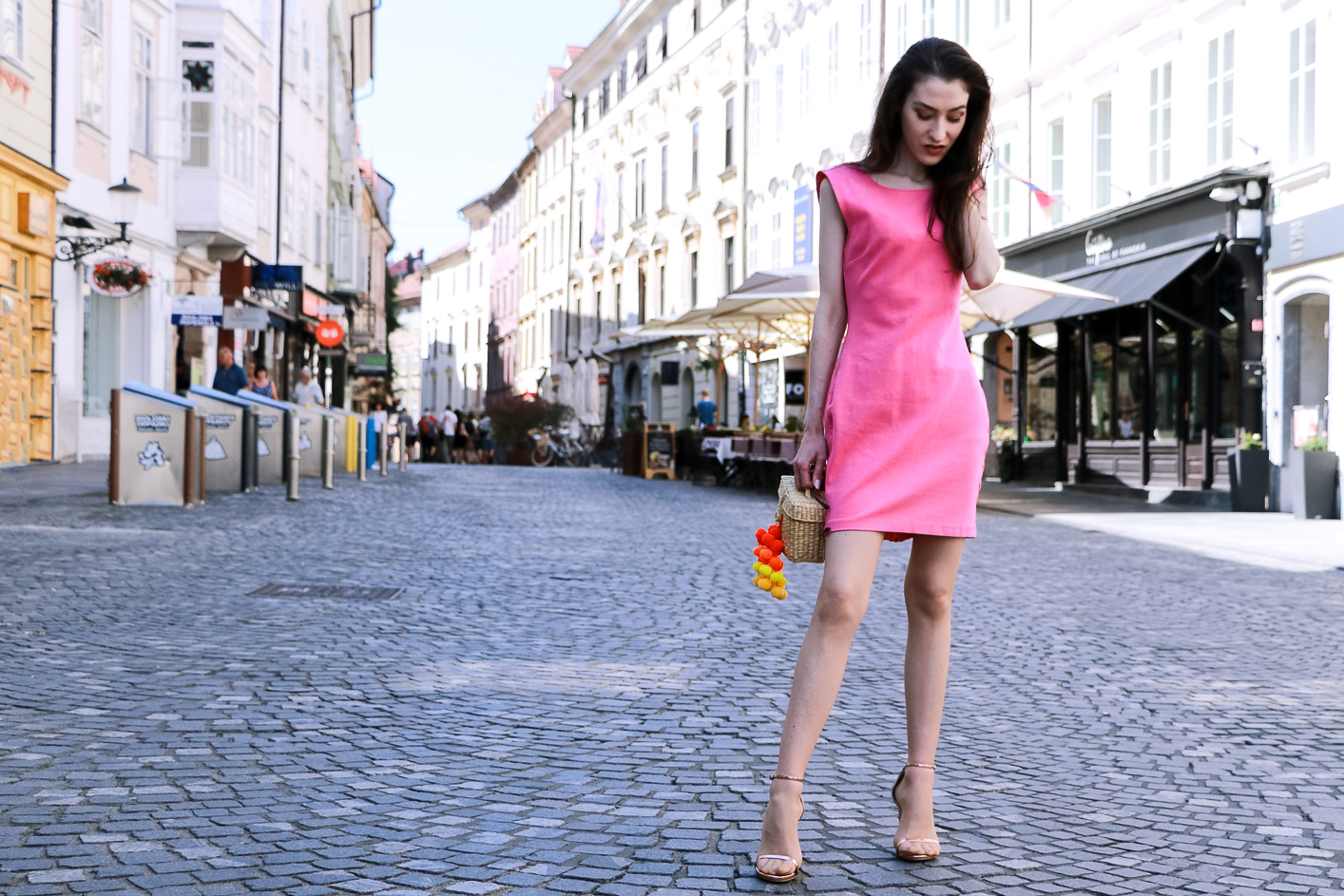 Fashion blogger Veronika Lipar of Brunette From Wall Street sharing how to style pink cocktail dress, rose gold sandals and raffia bag like a girl boss