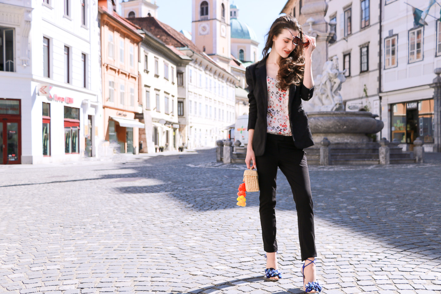 Fashion blogger Veronika Lipar of Brunette From Wall Street sharing how to style feminine black pant suit and sandals for party this summer