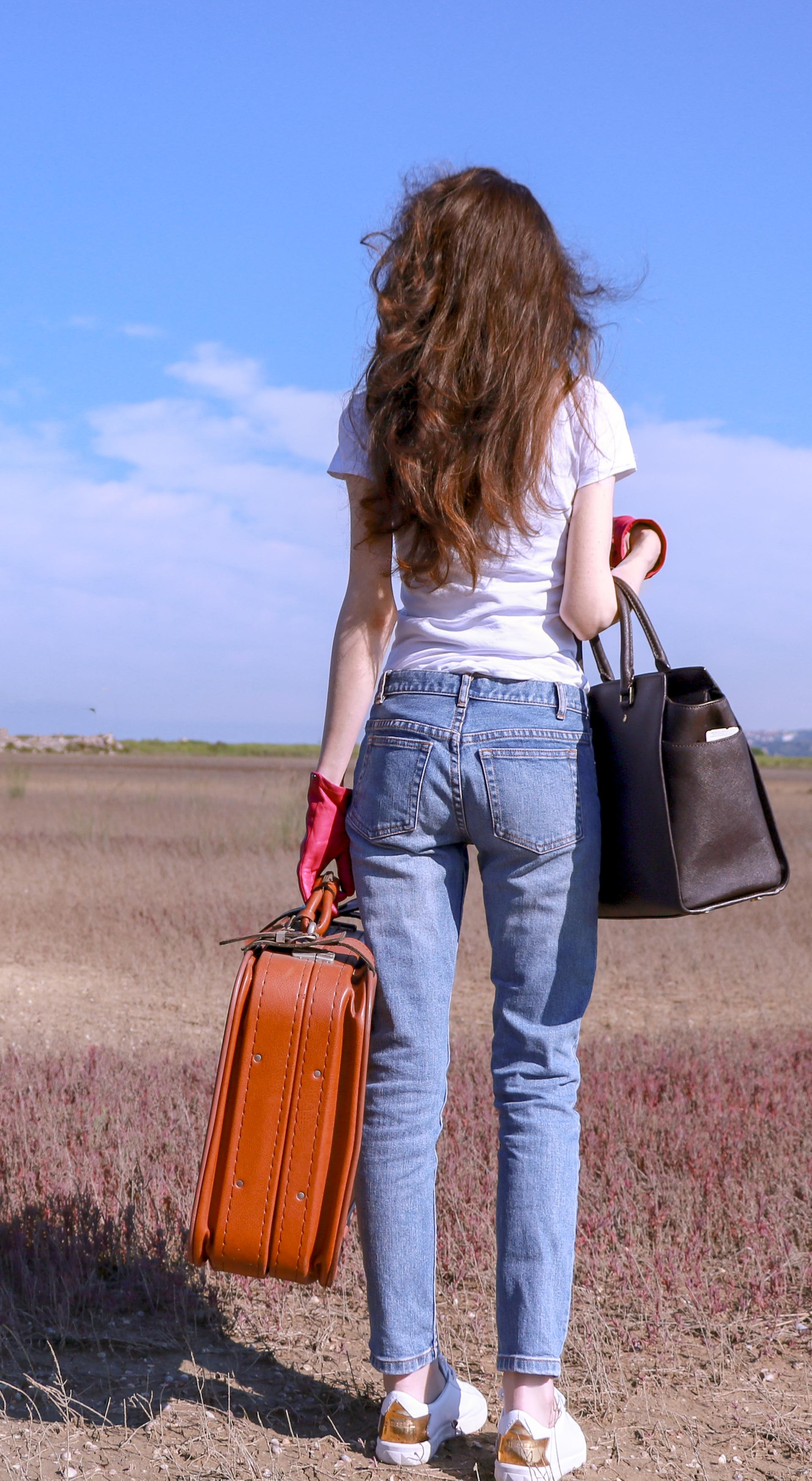 Popular fashion influencer Veronika Lipar of Brunette from Wall Street dressed in a.p.c. bleach denim jeans Diesel white sneakers white T-shirt pink leather gloves carrying Michael Kors sachets bag a vintage suitcase standing in the middle of nowhere