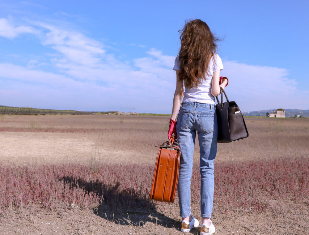 Popular fashion influencer Veronika Lipar of Brunette from Wall Street wearing a.p.c. bleach denim jeans Diesel white sneakers white T-shirt pink leather gloves carrying Michael Kors sachets bag a vintage suitcase standing in the middle of nowhere